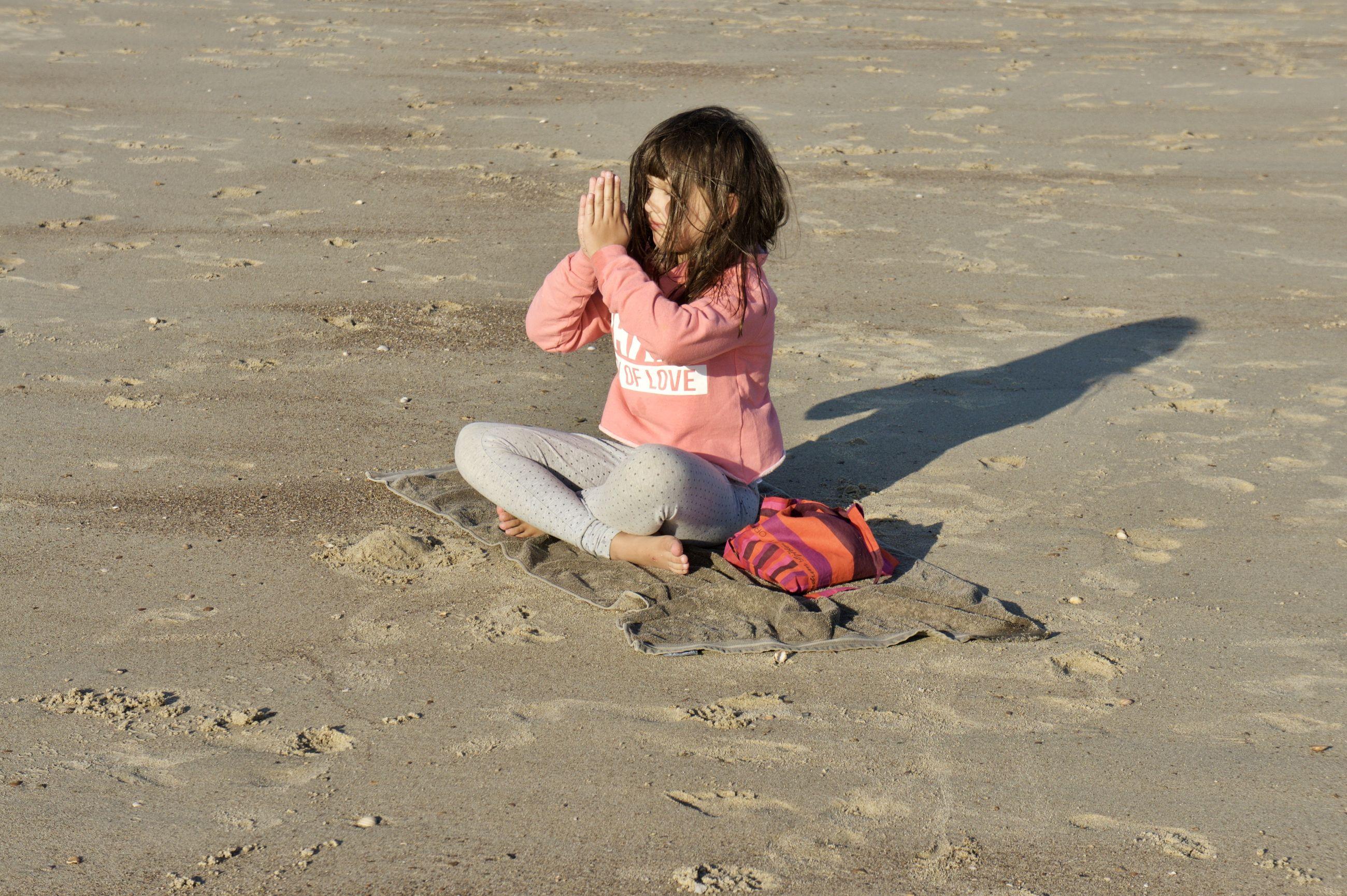 Girl practicing yoga at beach