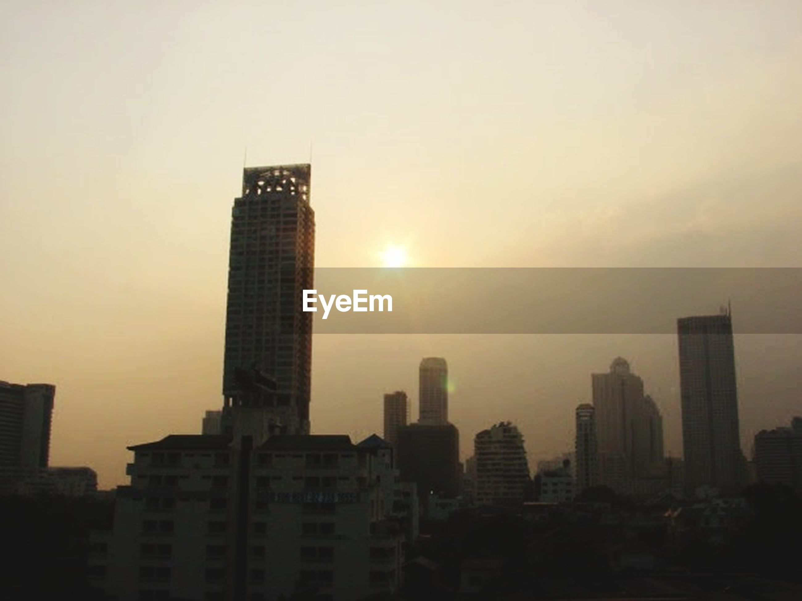 architecture, building exterior, built structure, city, building, skyscraper, office building exterior, sky, tall - high, modern, cityscape, sunset, urban skyline, sun, landscape, tower, nature, city life, residential district, no people, outdoors, financial district, smog