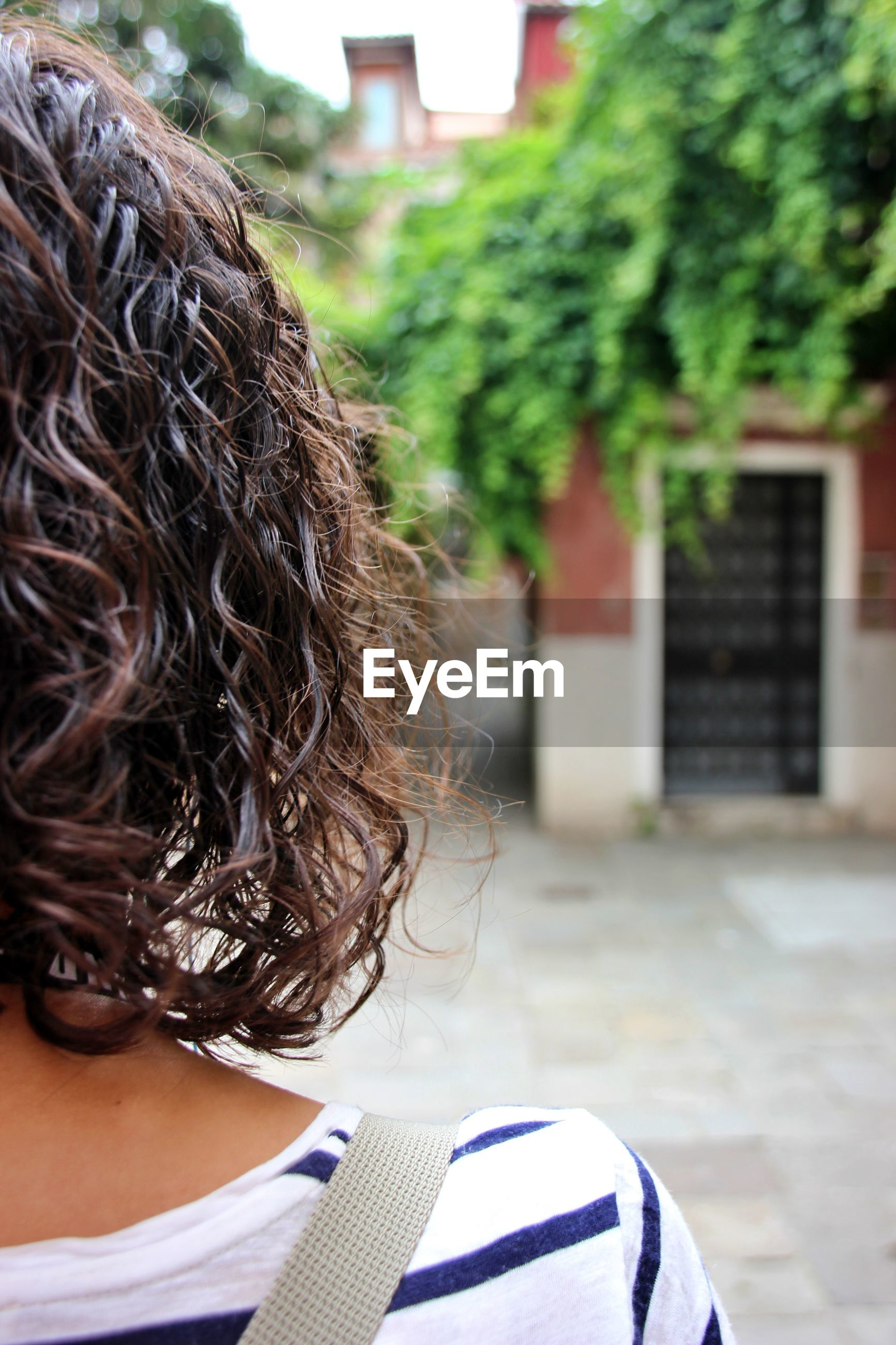 Rear view of woman with curly hair against tree