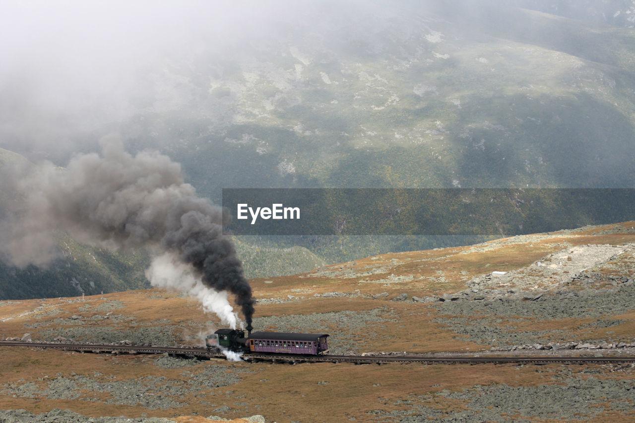 High Angle View Of Train Emitting Smoke While Moving Against Mountain