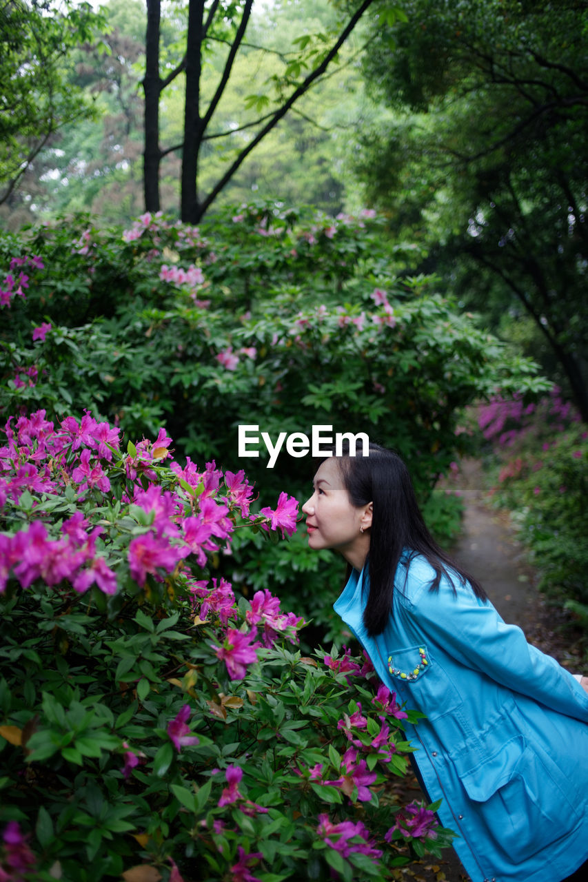 flower, plant, flowering plant, one person, young adult, growth, young women, freshness, vulnerability, nature, lifestyles, real people, fragility, side view, leisure activity, beauty in nature, women, day, casual clothing, adult, pink color, hair, hairstyle, outdoors, beautiful woman
