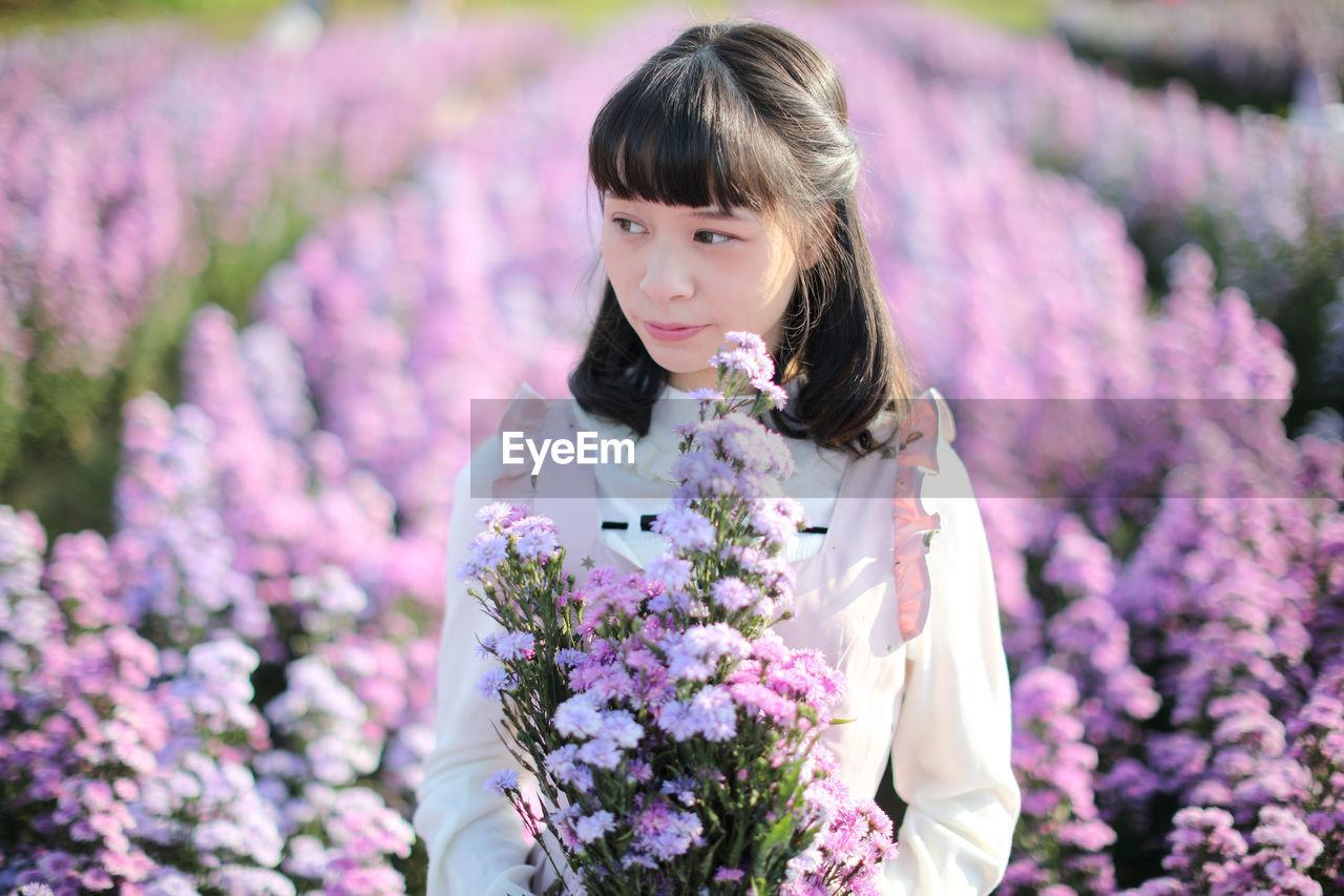 Beautiful woman looking away while standing by purple flowering plants