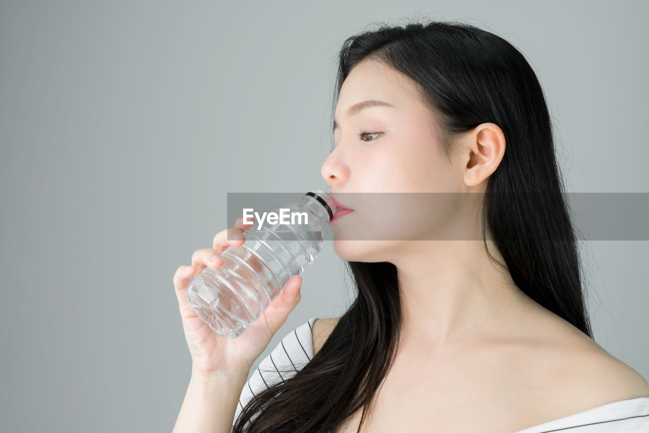 Woman drinking water from bottle against gray background