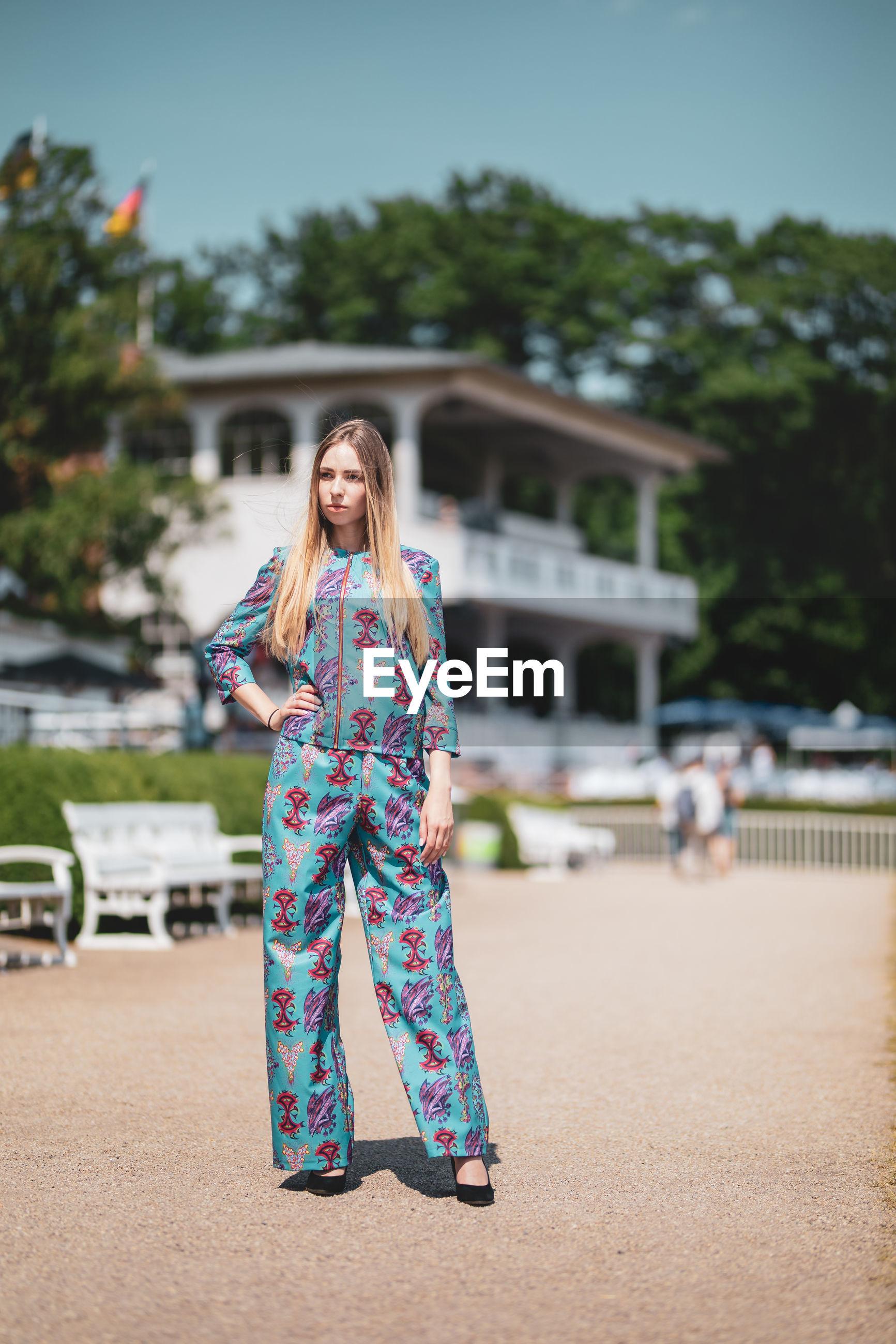 Female model standing on field against building
