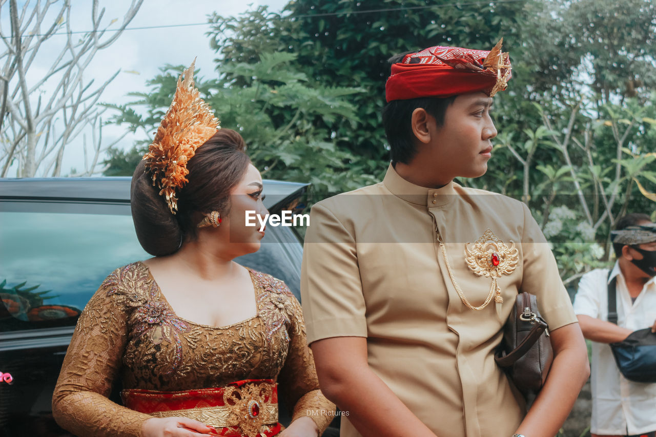 YOUNG COUPLE LOOKING AWAY IN A TRADITIONAL CLOTHING