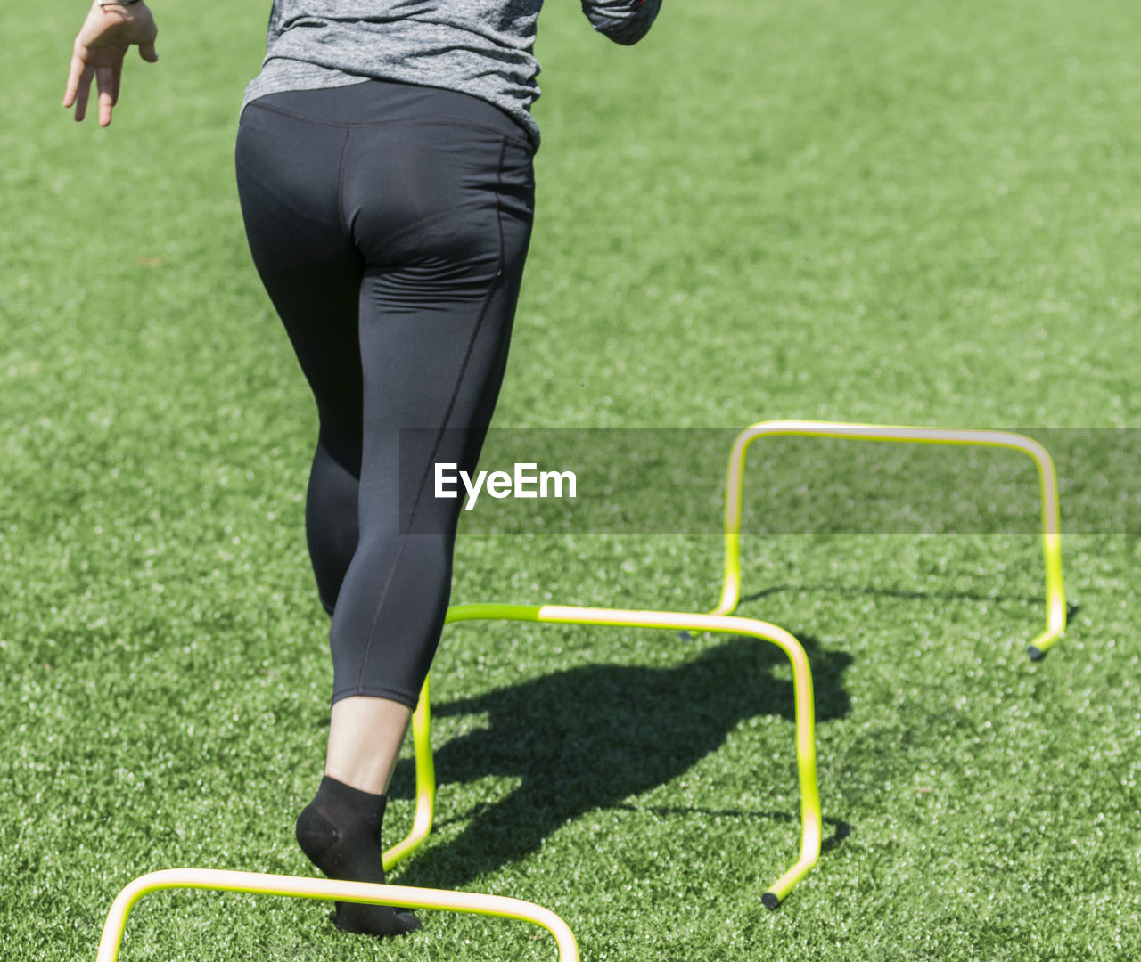 Rear view of woman running over hurdles on turf
