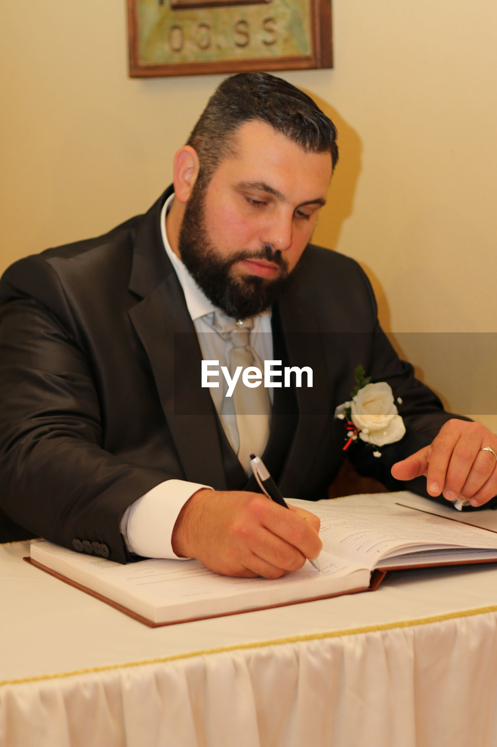 Groom writing in book while sitting at table