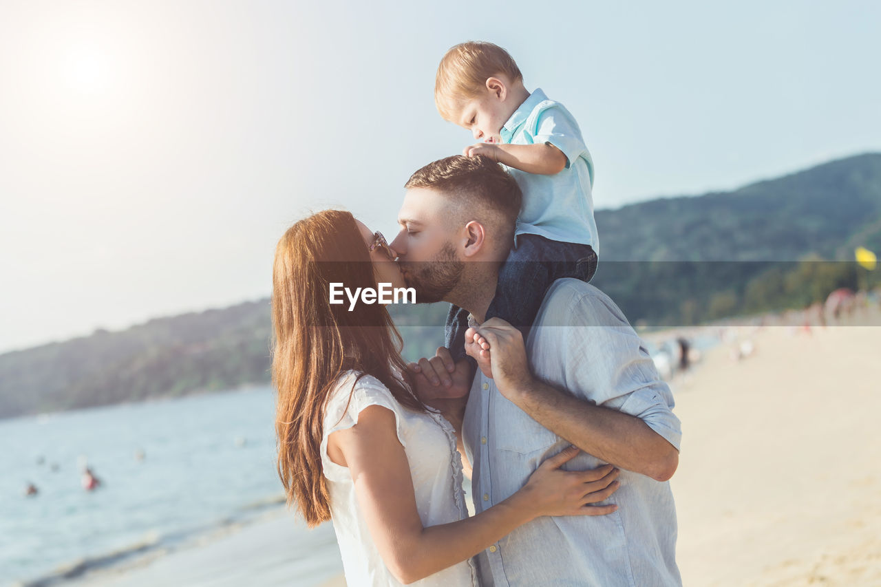 Couple kissing with son while standing at beach against sky