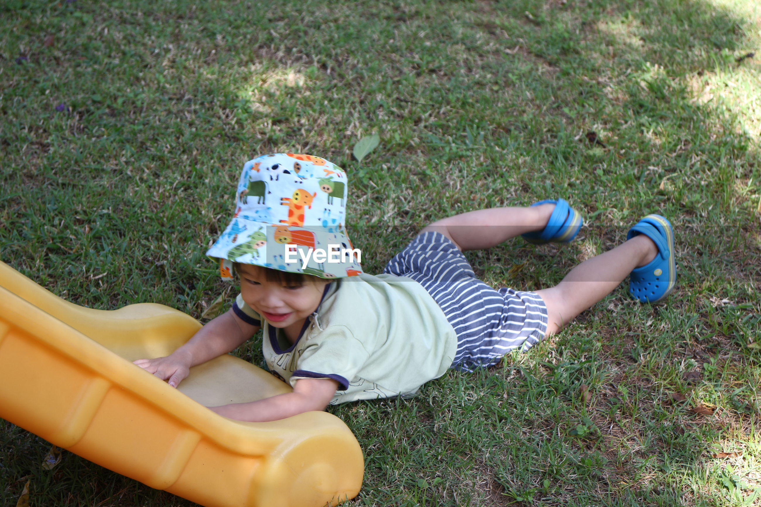 High angle view portrait of boy playing on grass
