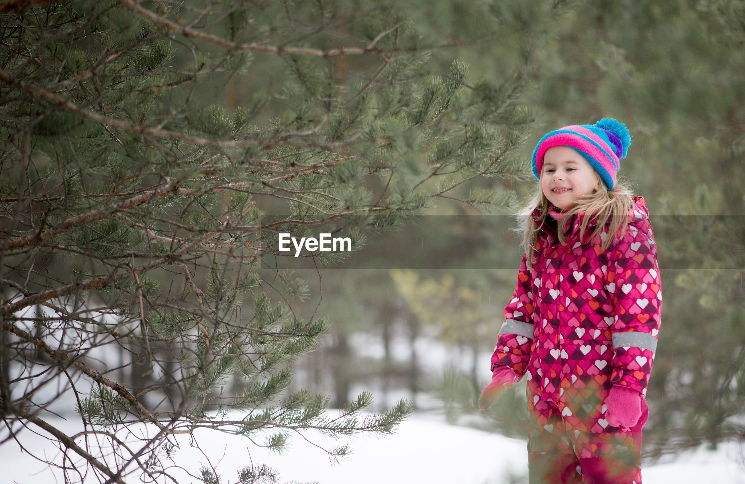Girl smiling while standing on snowy field by trees