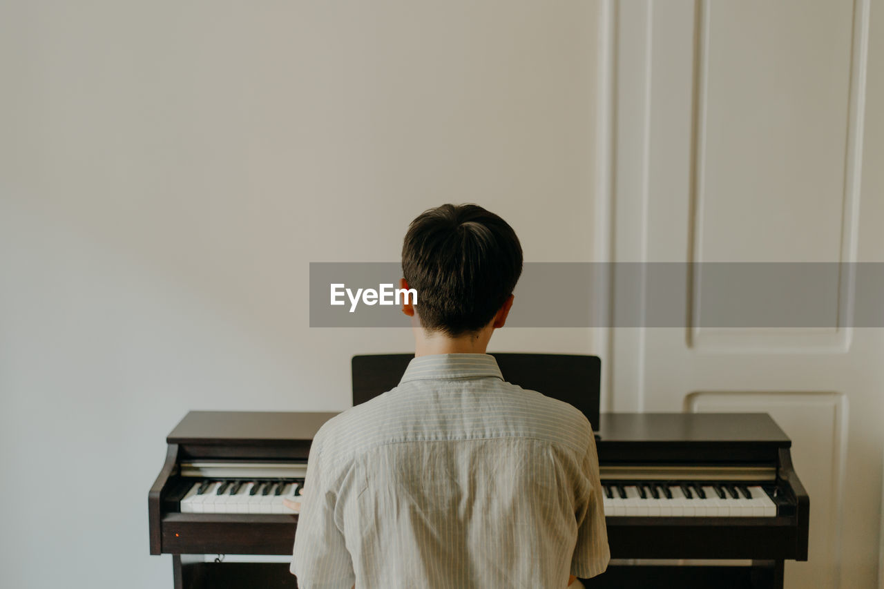 Rear view of a young man playing piano