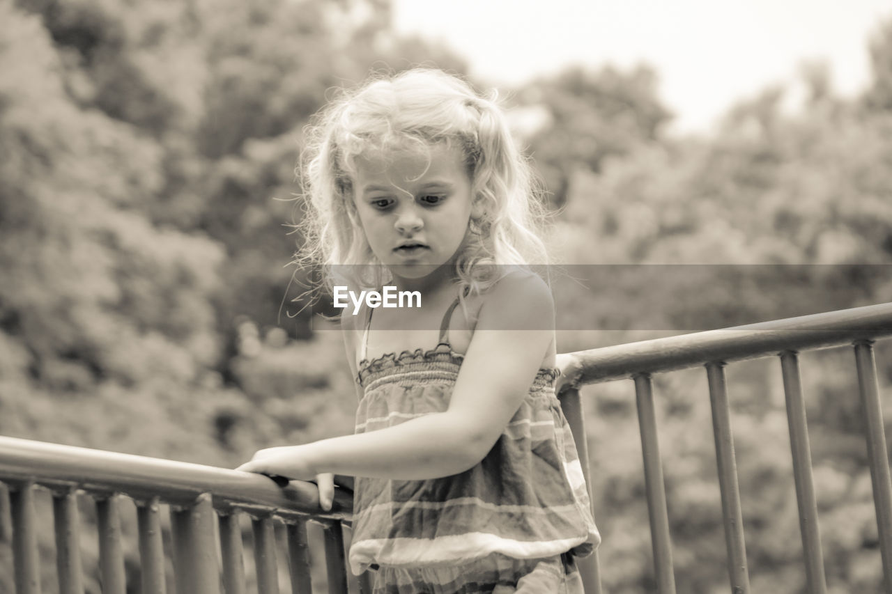 childhood, railing, girls, real people, one person, innocence, focus on foreground, elementary age, casual clothing, front view, cute, blond hair, outdoors, leisure activity, portrait, day, looking at camera, standing
