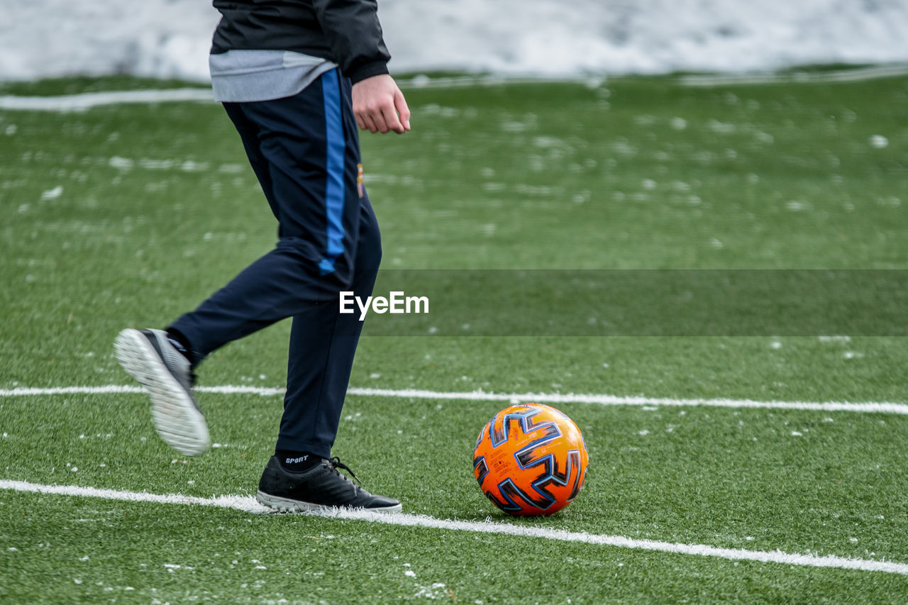 Low section of man playing soccer ball on grass