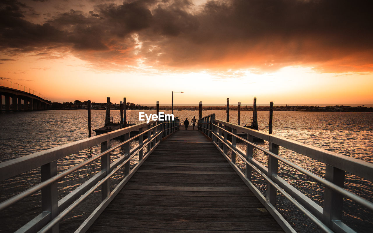 sky, water, sunset, the way forward, direction, railing, cloud - sky, nature, beauty in nature, scenics - nature, orange color, architecture, wood - material, built structure, connection, tranquil scene, pier, tranquility, sea, diminishing perspective, no people, outdoors, sun