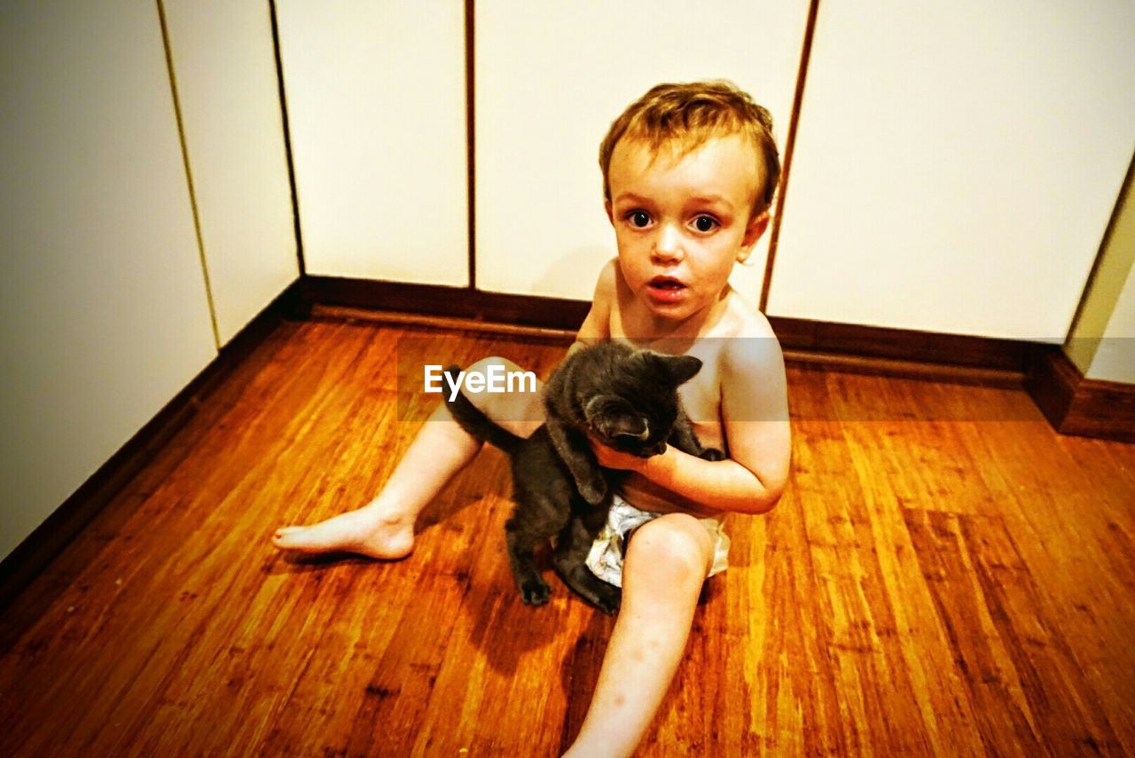 Portrait of boy holding cat while sitting on floor at home