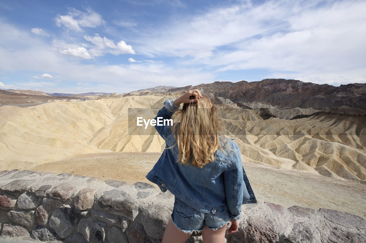 Rear View Of Woman With Hand In Hair Standing At Desert