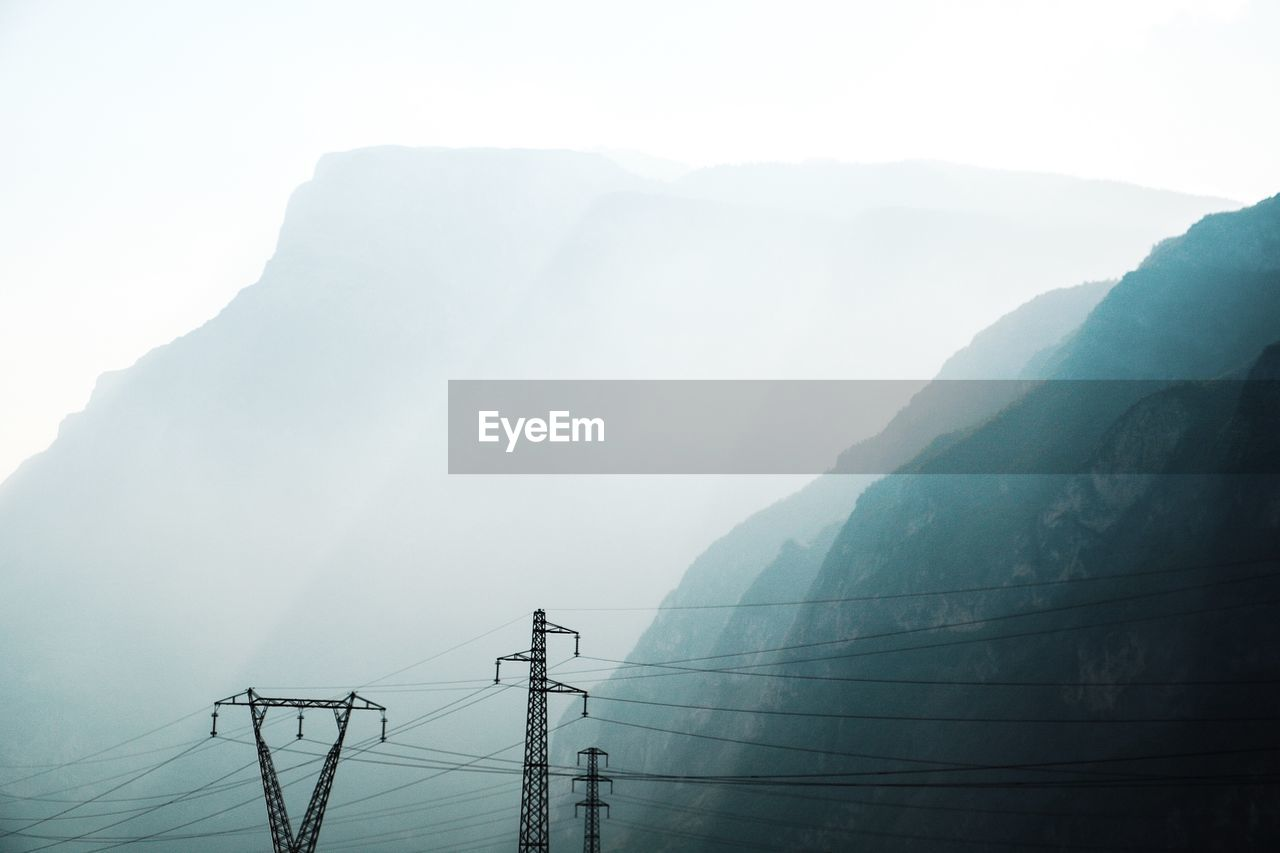 Electricity Pylon On Mountain Against Sky During Foggy Weather