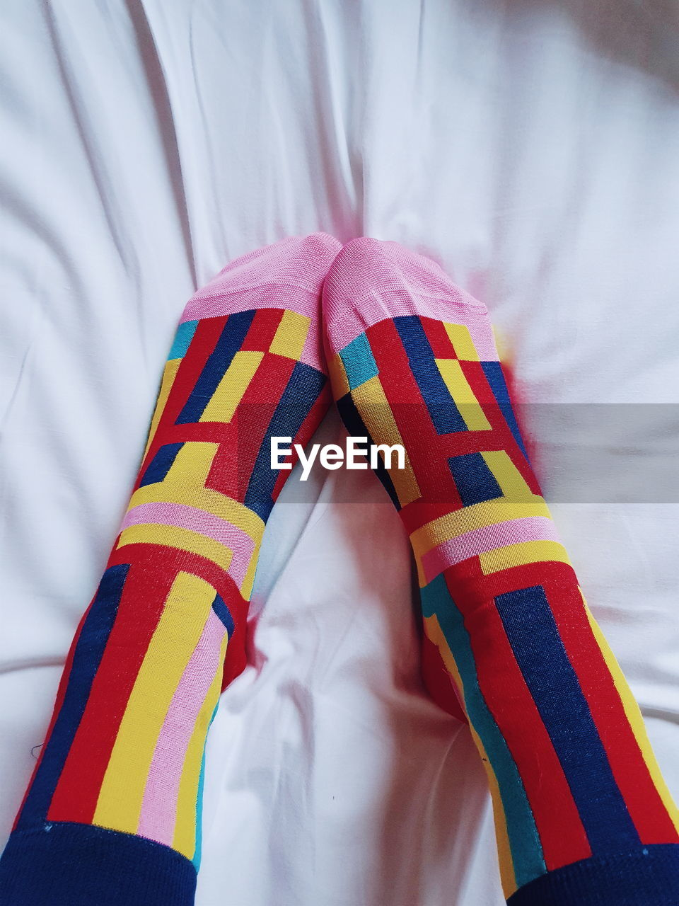 Low section of person wearing socks on bed