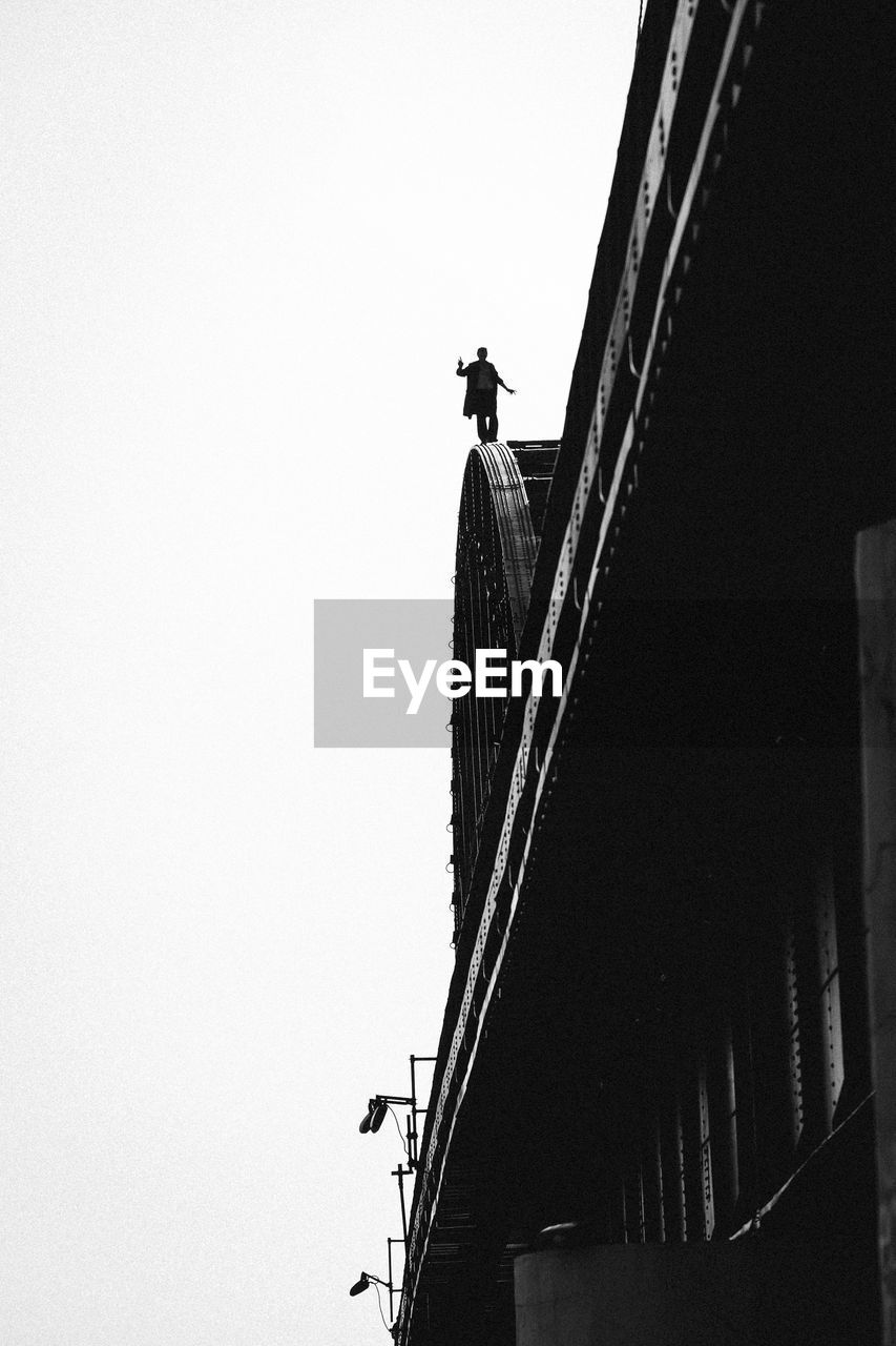architecture, sky, built structure, low angle view, clear sky, copy space, men, real people, nature, building exterior, people, day, full length, outdoors, lifestyles, unrecognizable person, bridge, connection, staircase