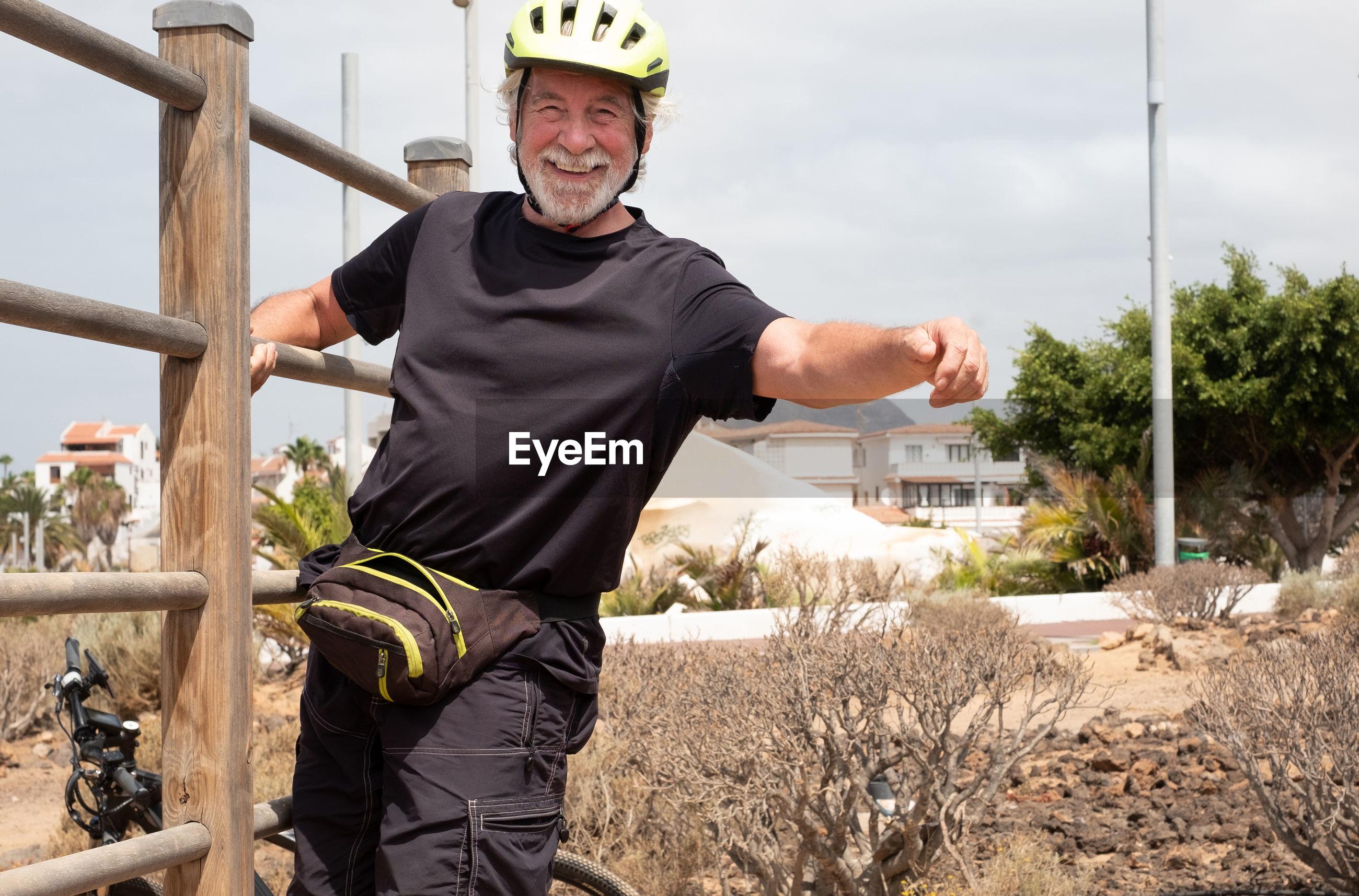 Portrait of smiling senior man standing by railing against sky