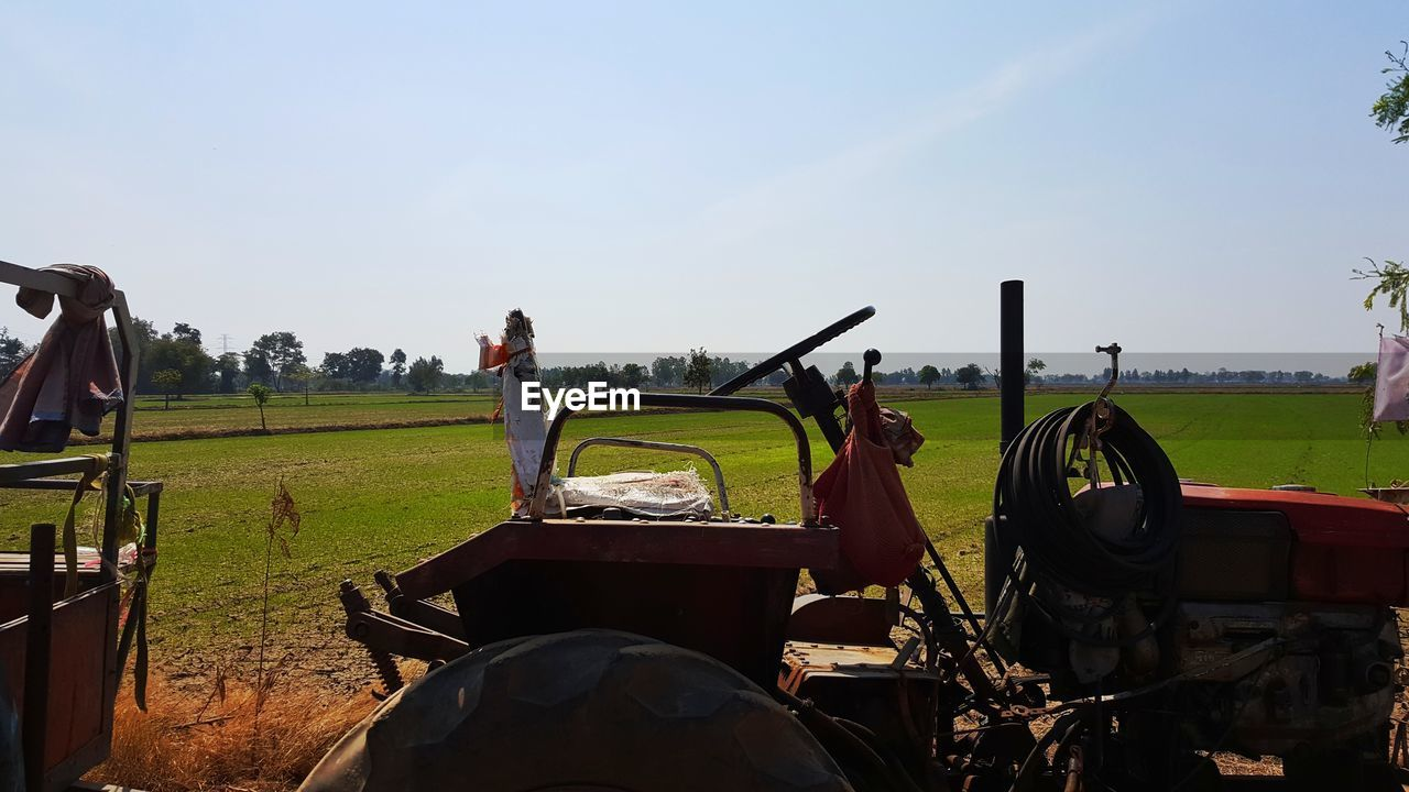 field, transportation, land vehicle, grass, mode of transport, sky, tree, day, tractor, agriculture, nature, real people, landscape, car, men, outdoors, clear sky, beauty in nature, one person, golf course, people