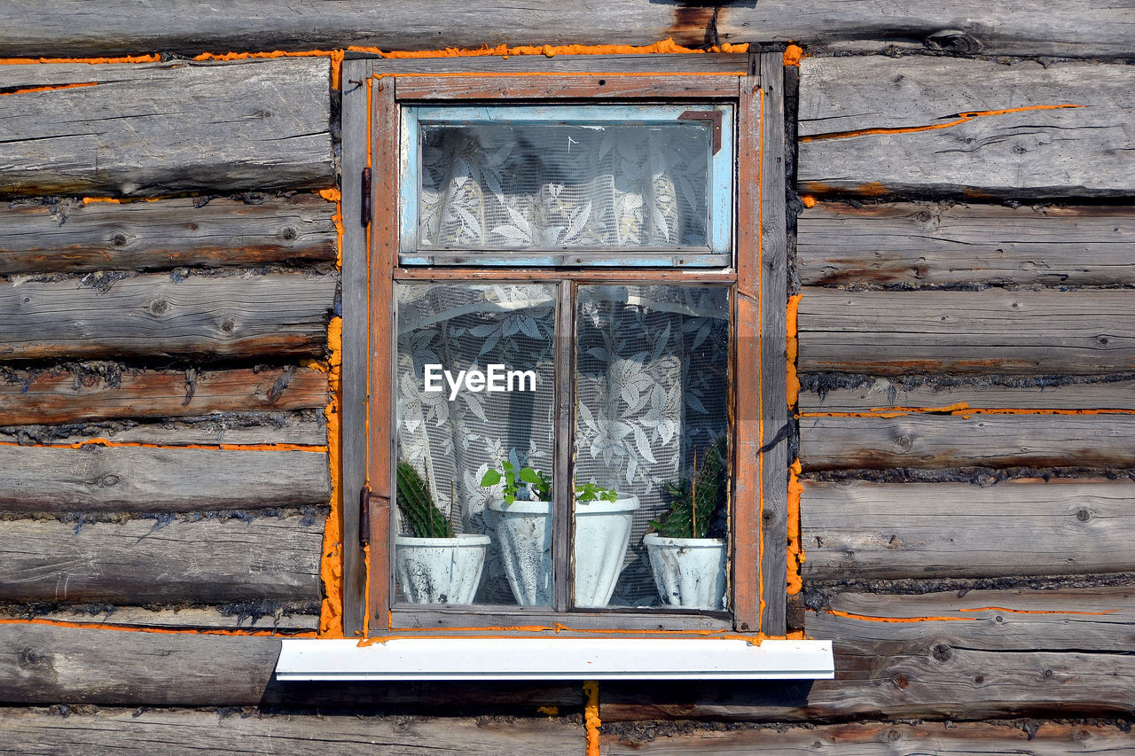 wood - material, day, no people, architecture, built structure, building exterior, outdoors, wall - building feature, nature, brown, building, potted plant, weathered, window, wood, transparent, plant, glass - material, closed, wall