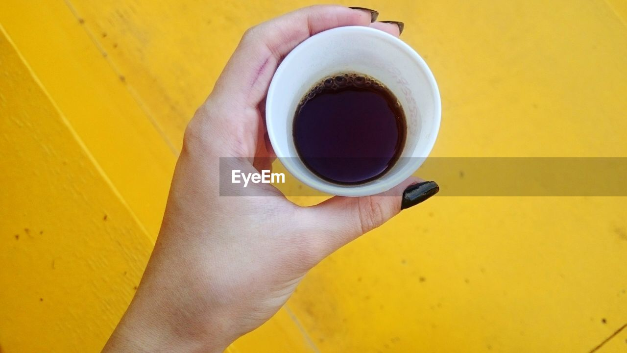 human hand, hand, cup, mug, drink, yellow, holding, food and drink, coffee, refreshment, coffee cup, coffee - drink, one person, real people, human body part, indoors, lifestyles, high angle view, freshness, finger, human limb, tea cup, non-alcoholic beverage