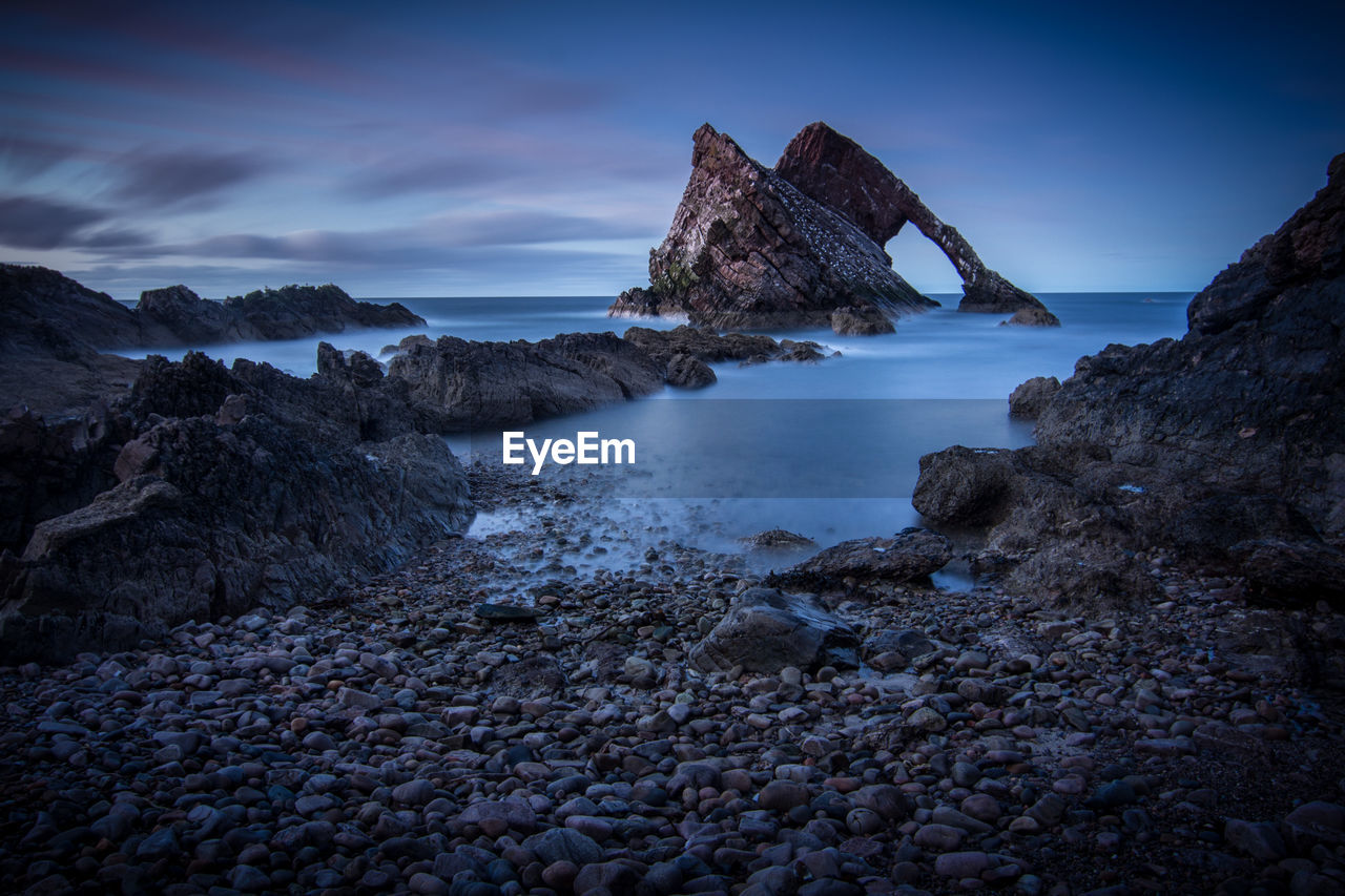 Scenic view of rock formations in sea against sky at dusk