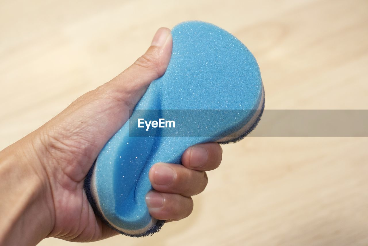 Cropped Hand Of Man Holding Sponge Over Wooden Table