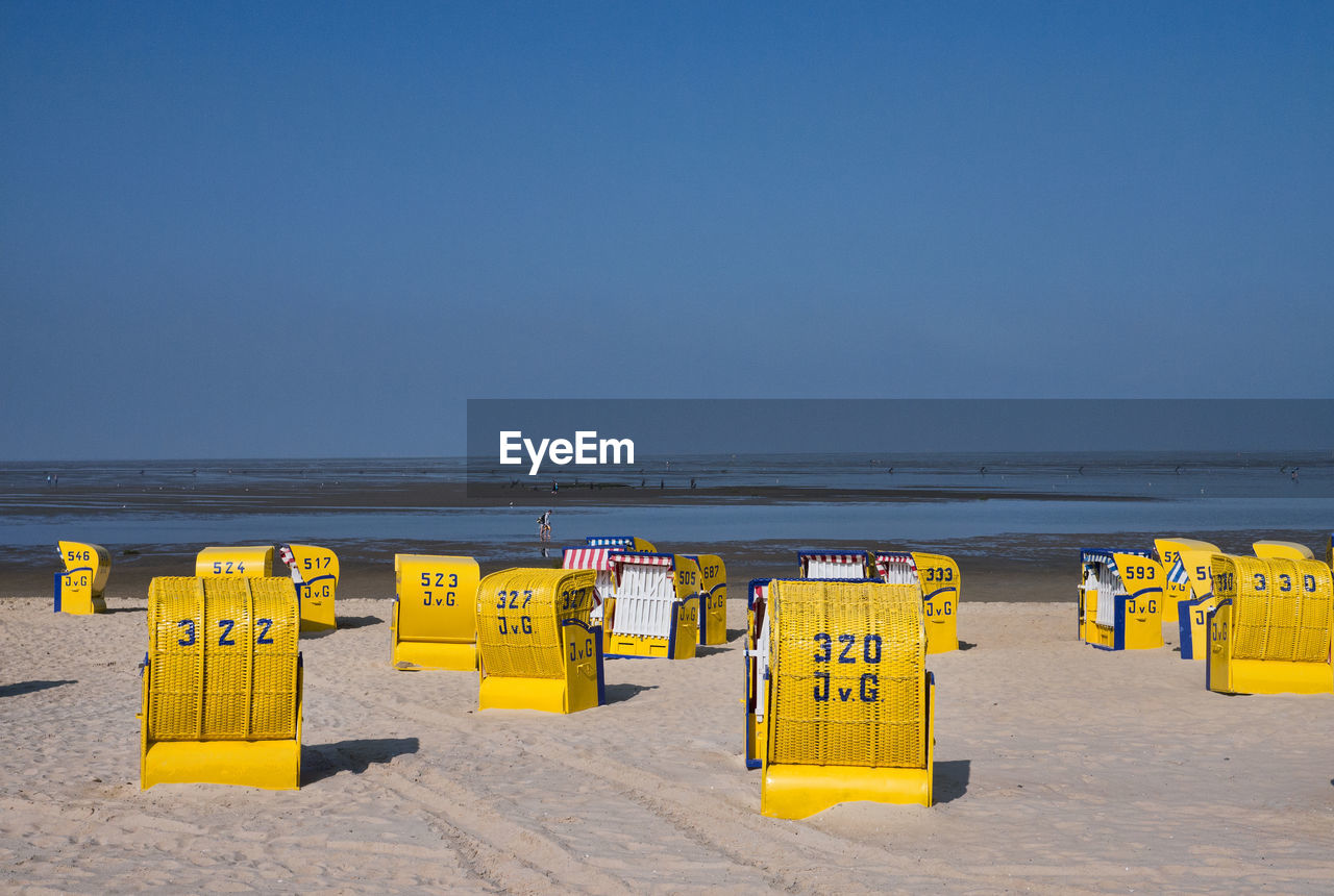 sea, beach, horizon over water, water, sand, nature, tranquility, scenics, beauty in nature, shore, day, tranquil scene, yellow, outdoors, sky, clear sky, copy space, in a row, sunlight, no people, summer, blue, vacations
