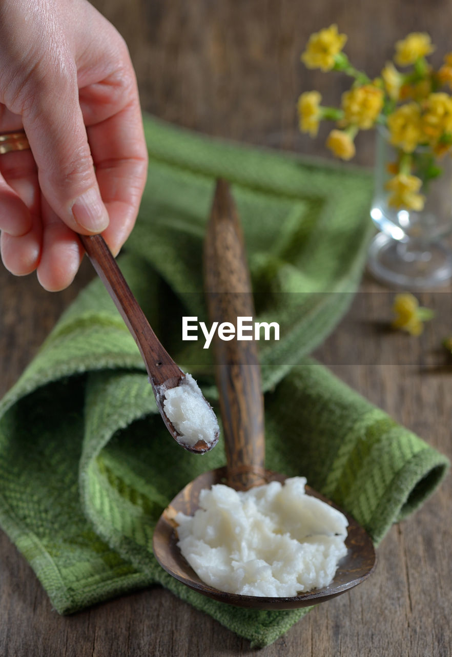 Close-Up Of Hand Holding Wooden Spoon With Butter On Table