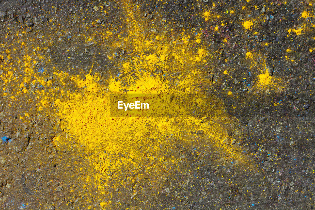 Close-Up Of Yellow Powder Paint On Footpath