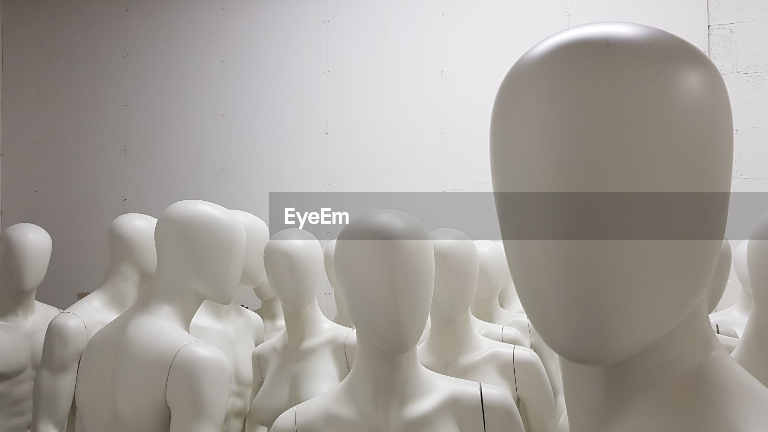 Close-up of mannequins against wall
