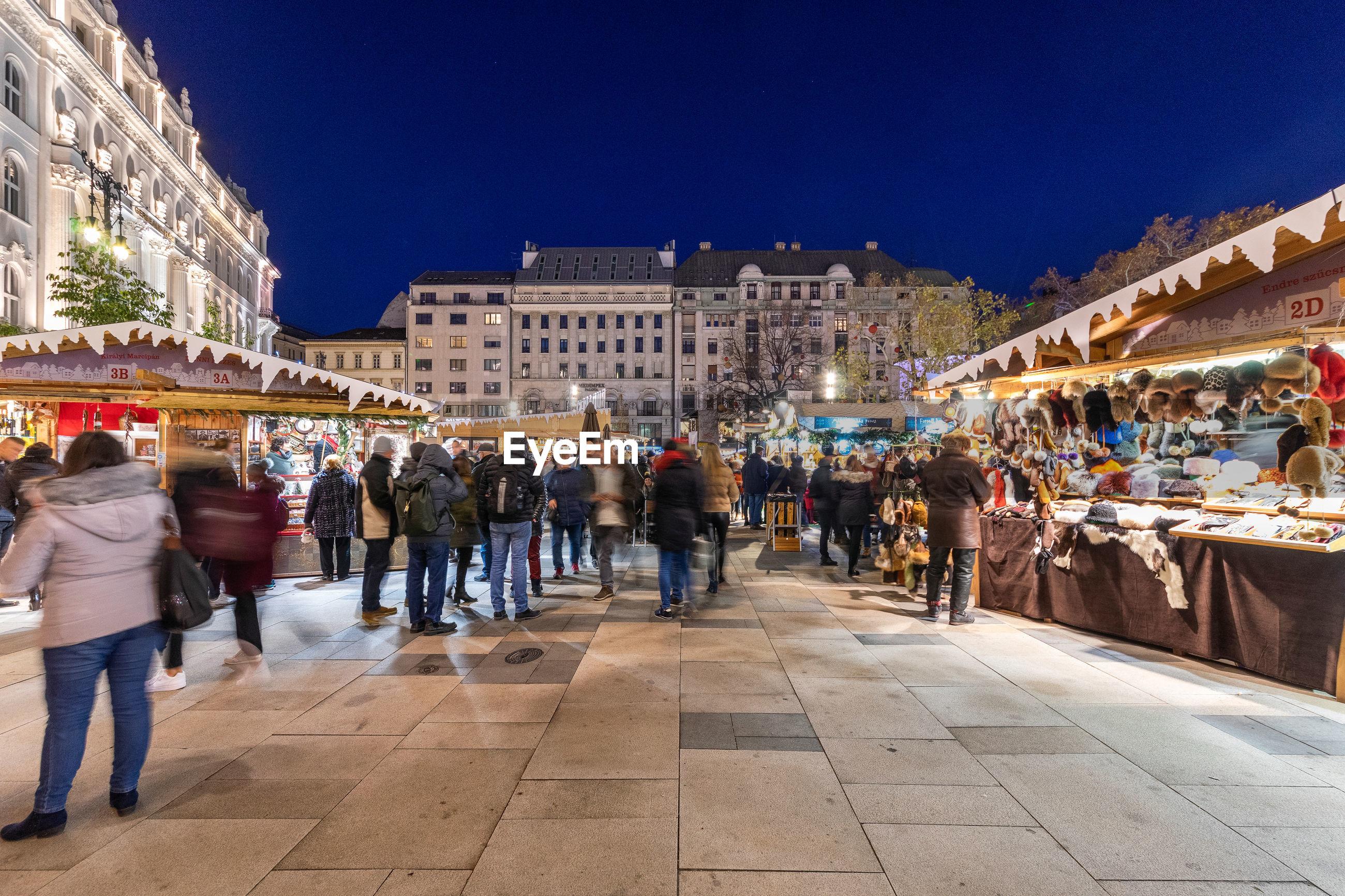 GROUP OF PEOPLE WALKING ON ILLUMINATED CITY AT NIGHT
