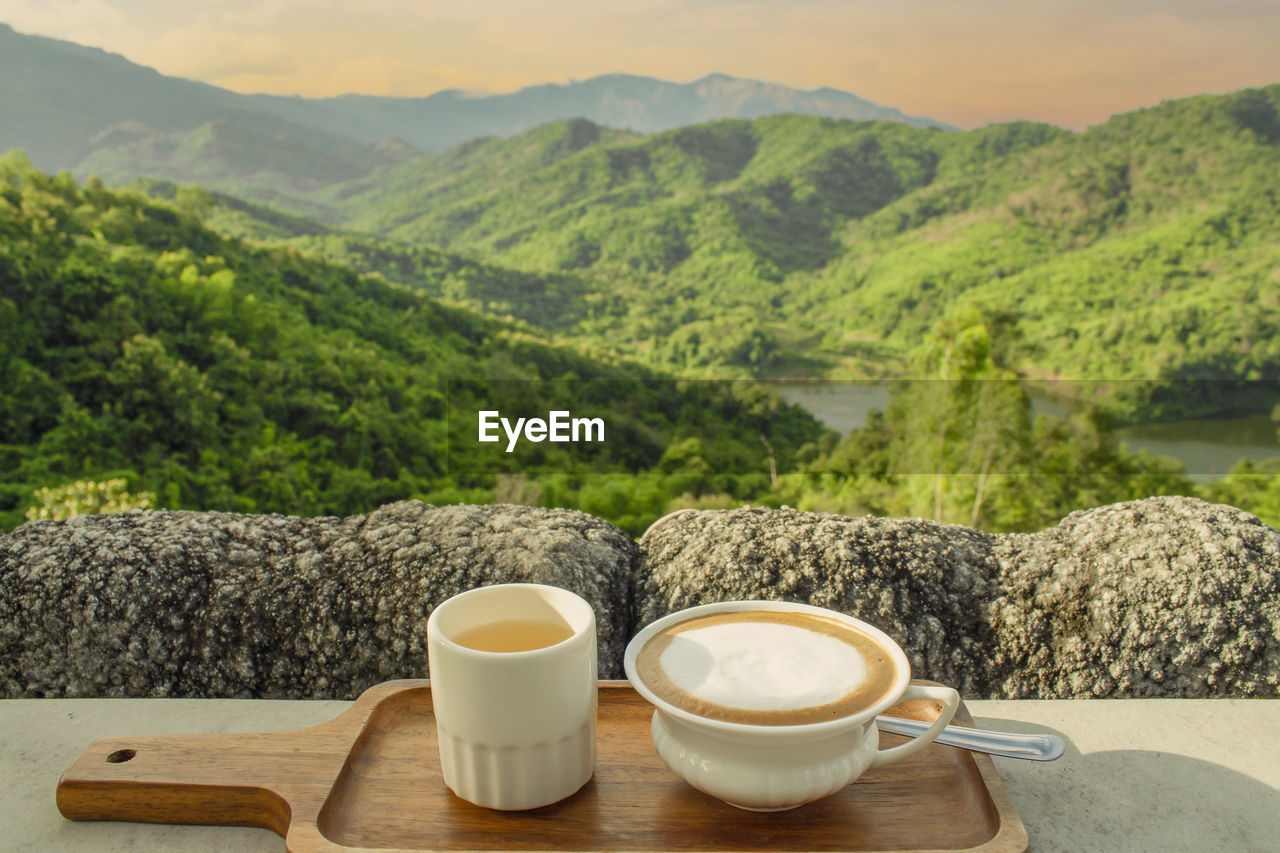 COFFEE CUP ON TABLE BY MOUNTAINS