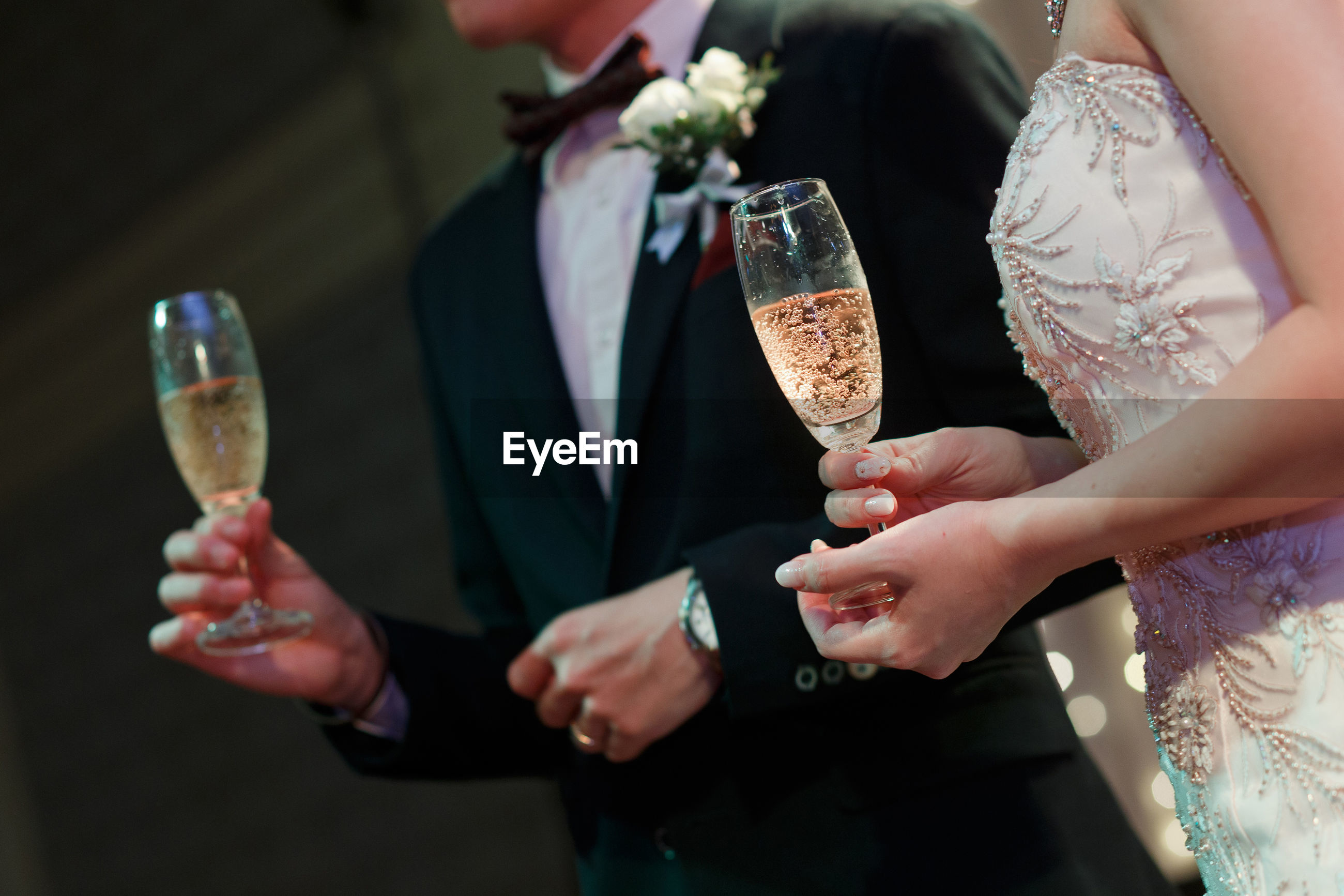 Midsection of bride and bridegroom having champagne during wedding ceremony