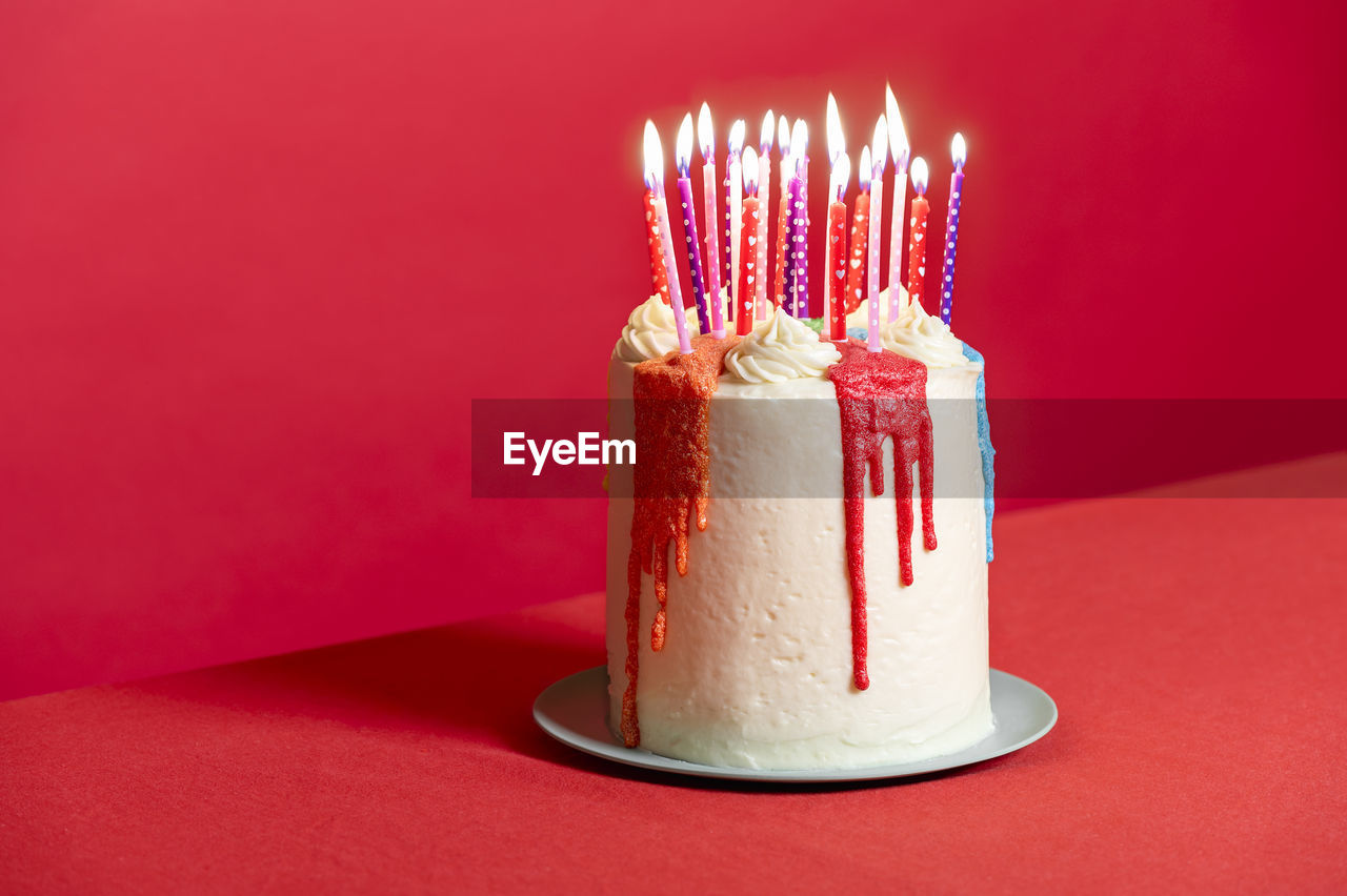 CLOSE-UP OF CAKE ON ILLUMINATED RED CANDLE