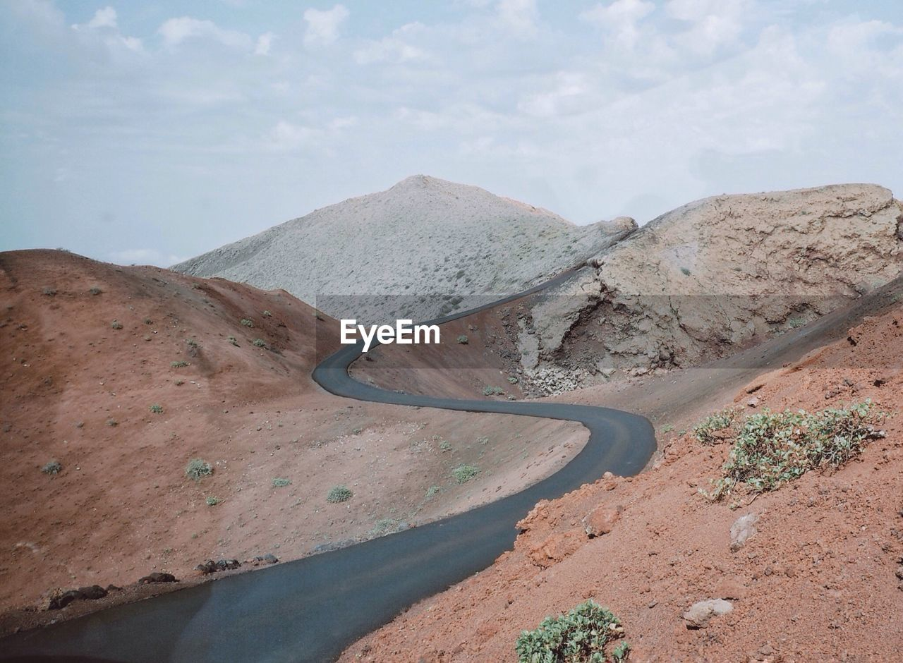 mountain, road, transportation, landscape, nature, non-urban scene, mountain road, day, scenics, sky, beauty in nature, winding road, high angle view, tranquility, no people, mountain range, outdoors, tranquil scene, physical geography, curve, arid climate