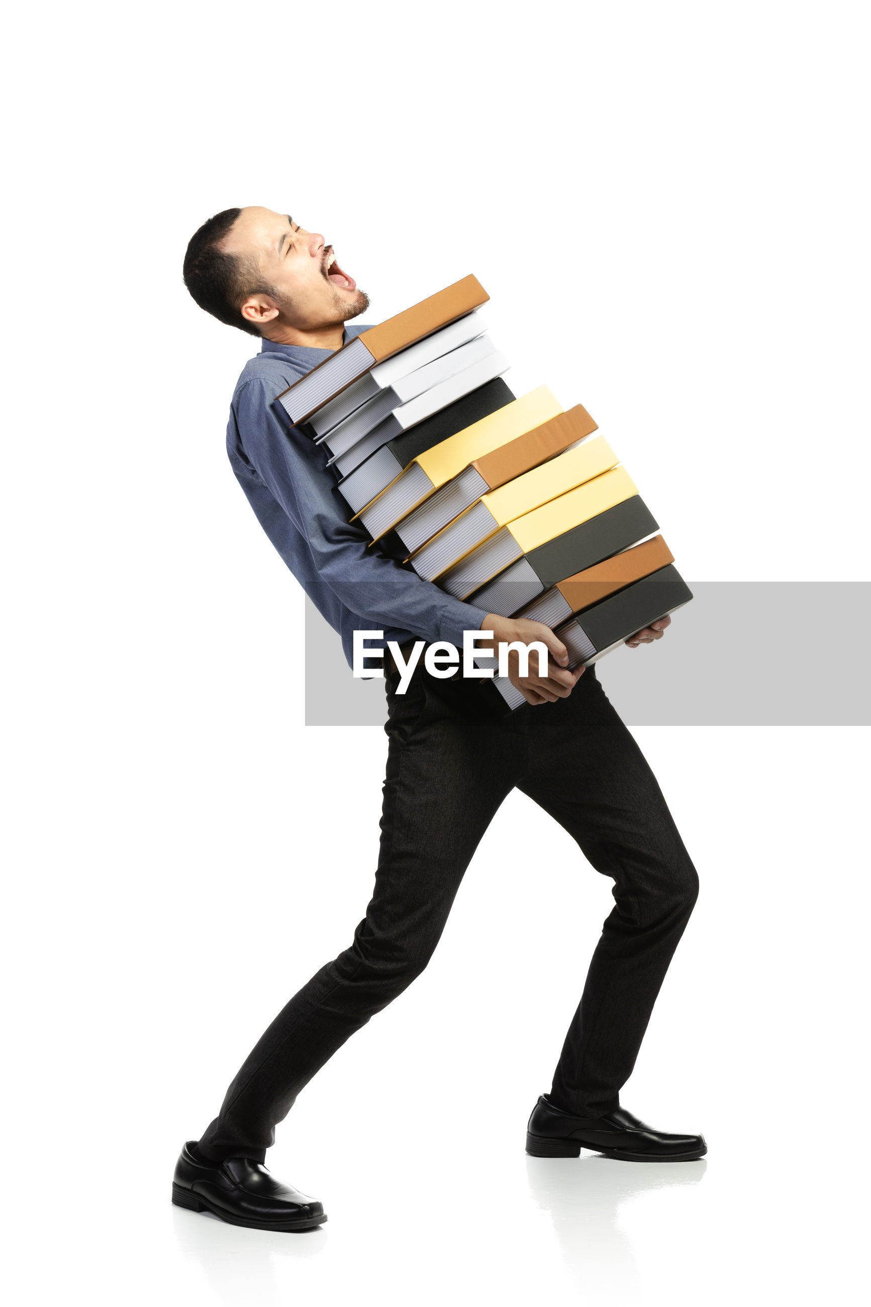 Full length of businessman carrying stacked books against white background
