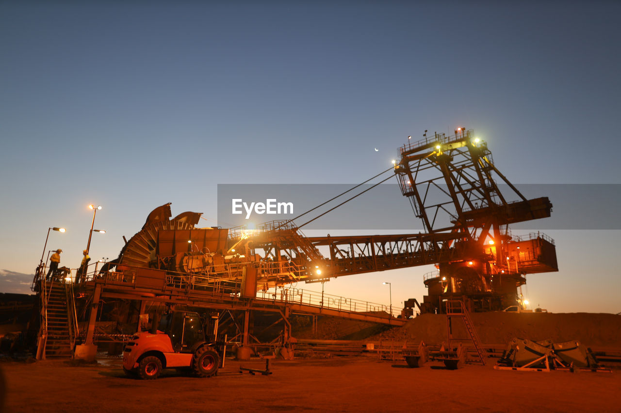 sky, industry, transportation, mode of transportation, machinery, nature, crane - construction machinery, clear sky, sunset, business, sunlight, illuminated, no people, outdoors, construction industry, architecture, sun, copy space, mining, orange color, industrial equipment, construction equipment