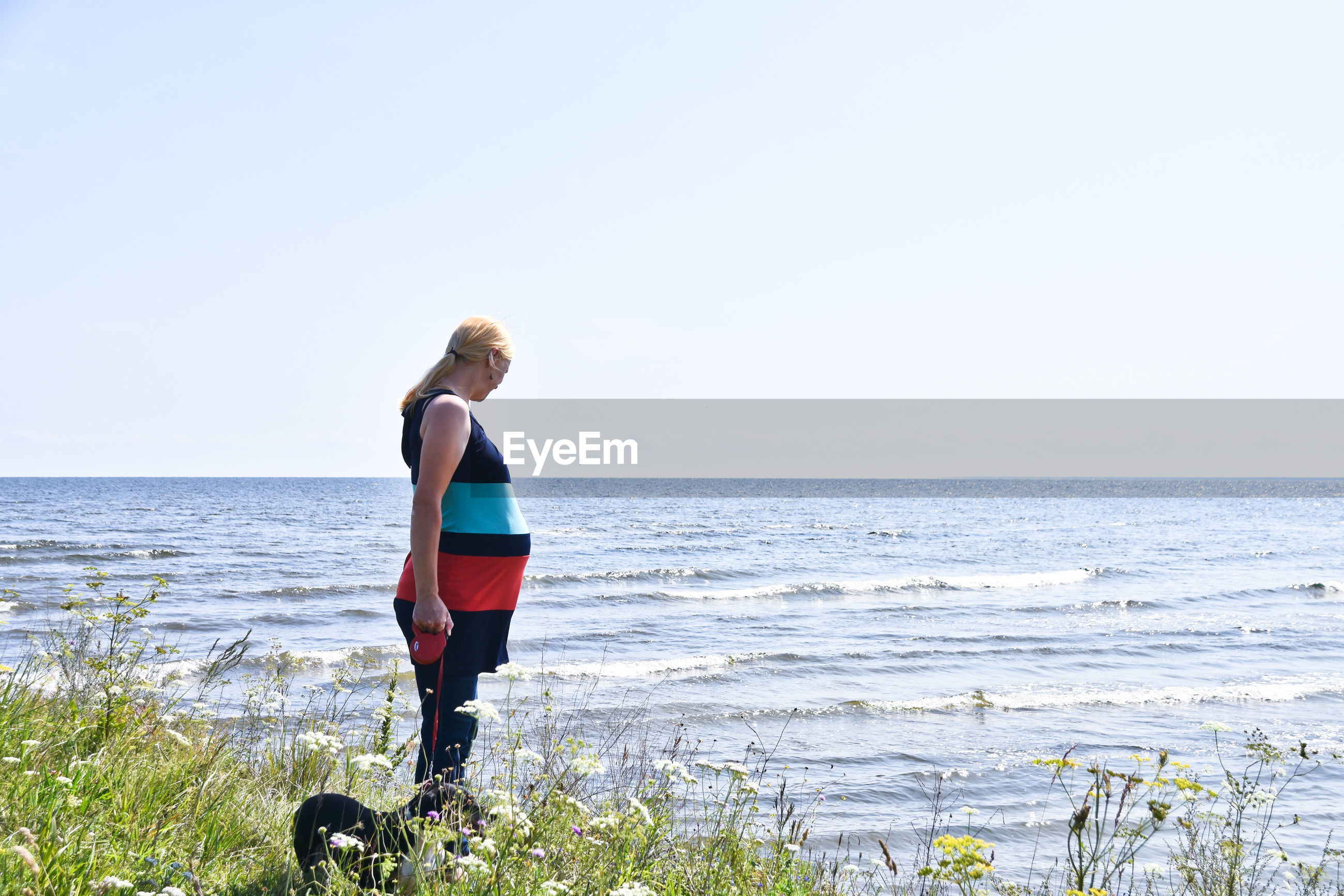 Pregnant woman standing on grass by sea against clear sky