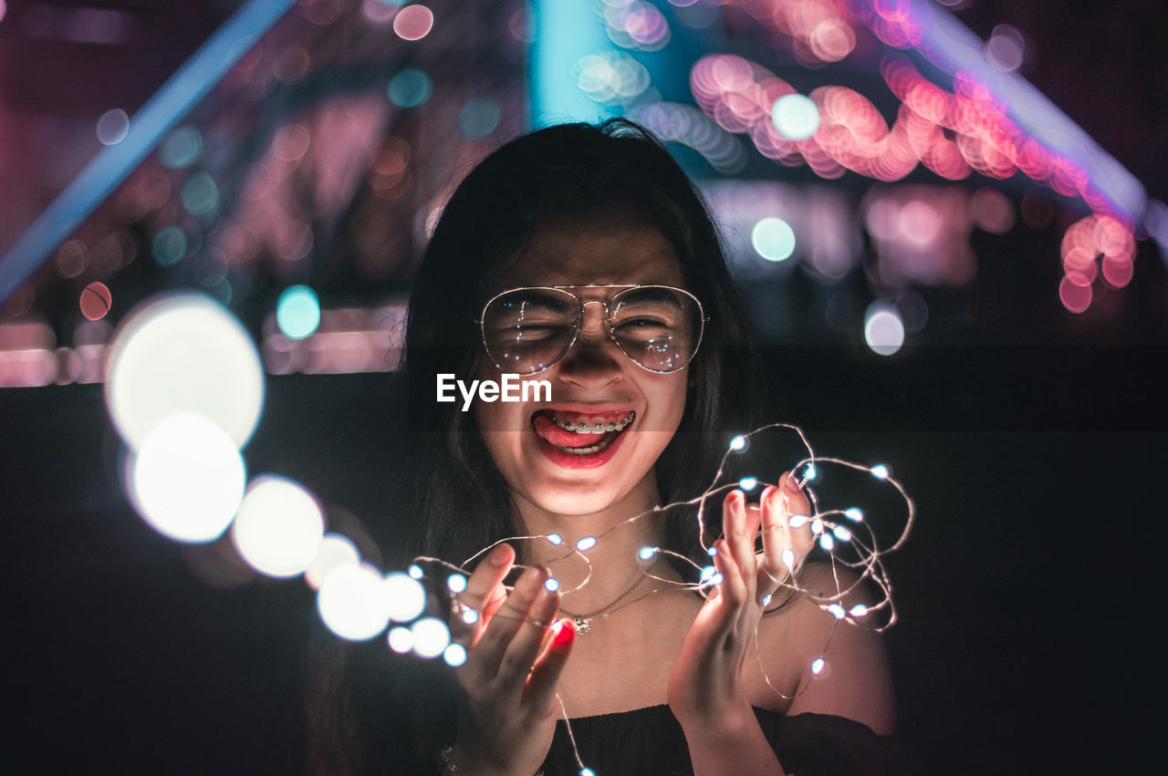 Portrait Of Smiling Woman Holding Illuminated Lights