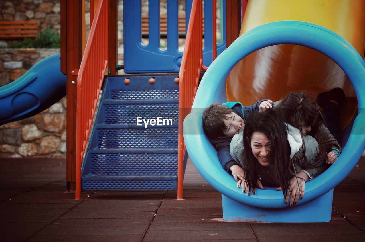 Portrait Of Happy Mother With Children In Slide At Playground