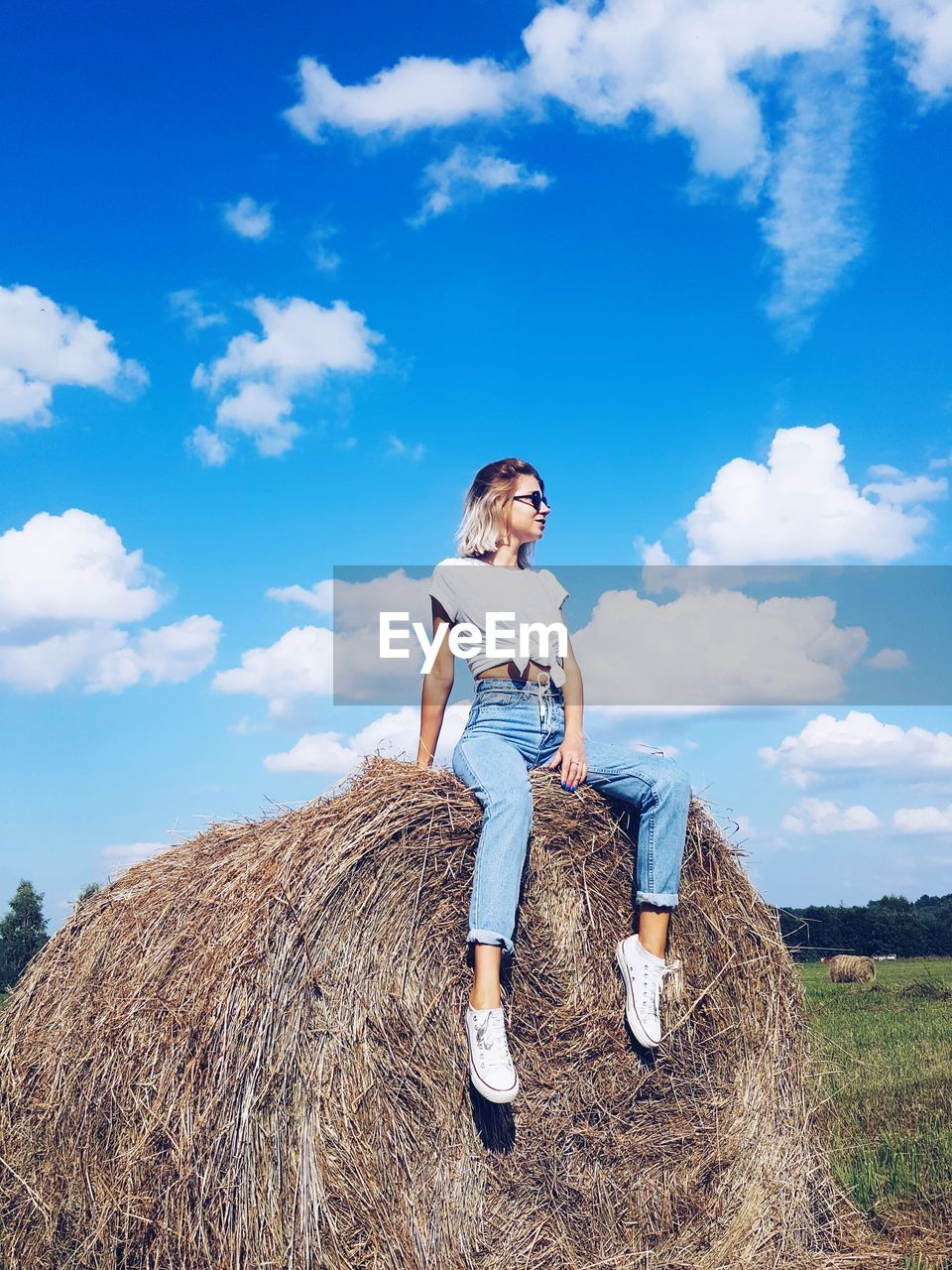 Full Length Of Young Woman Sitting On Hay Bale In Field