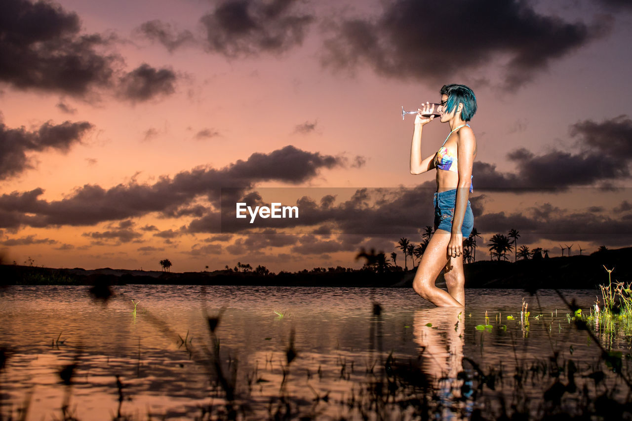 Side View Of Young Woman Drinking Wine While Standing In Lake During Sunset
