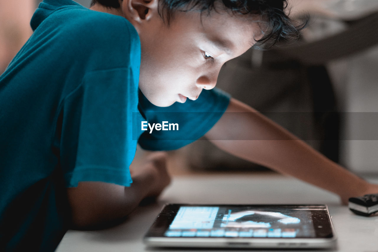Close-up of boy using digital tablet at table