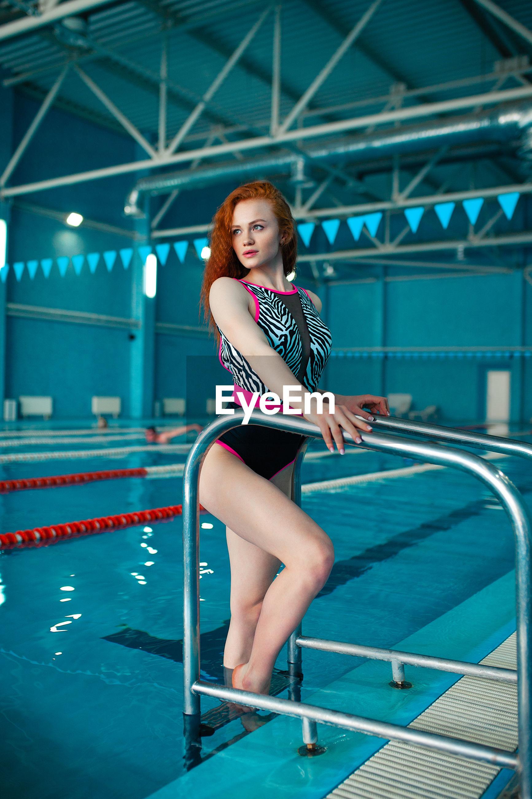 Beautiful redhead woman standing in swimming pool