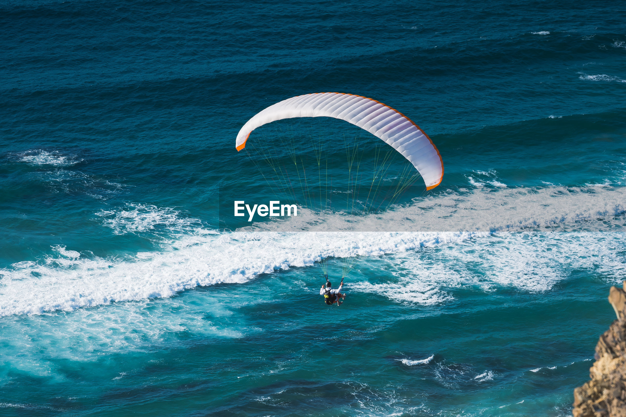 Rear view of man paragliding over sea