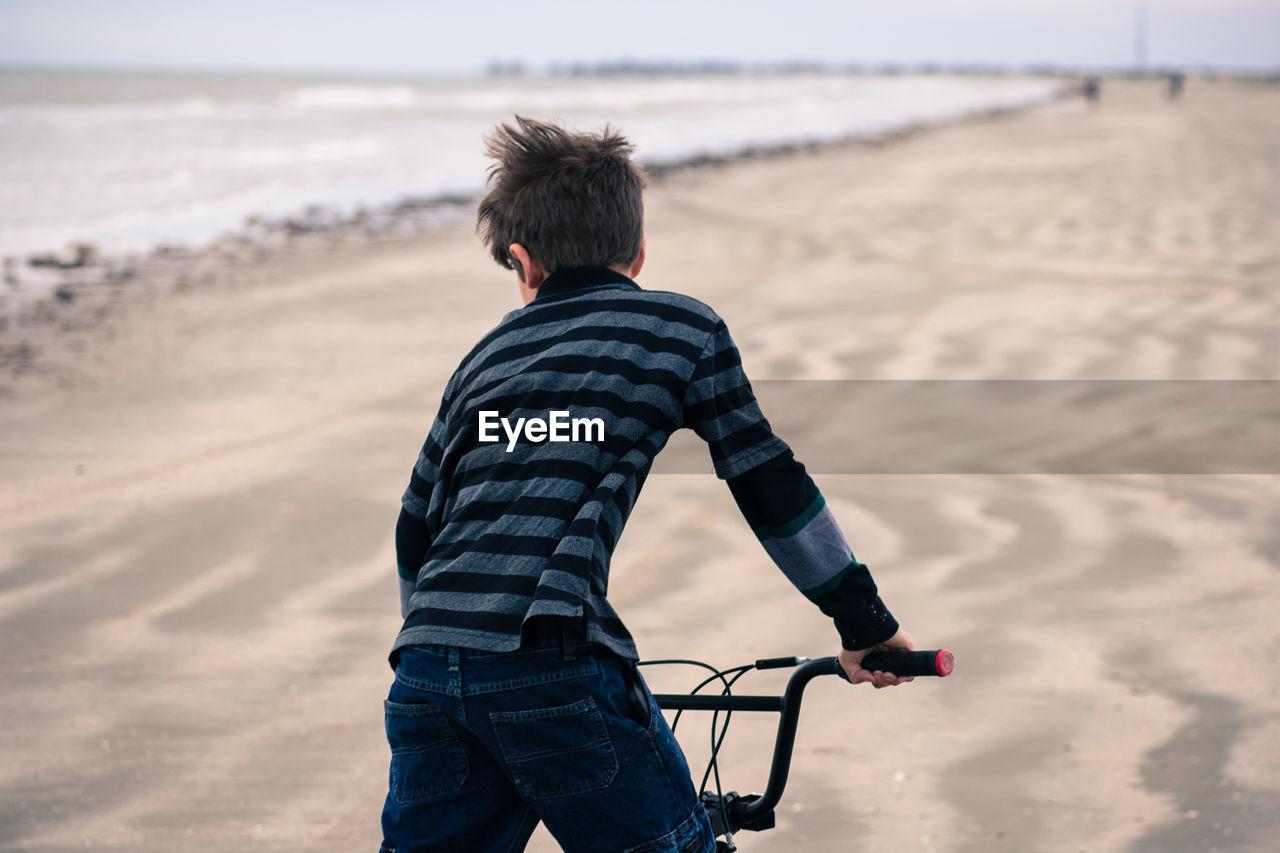 Rear view of boy cycling at beach