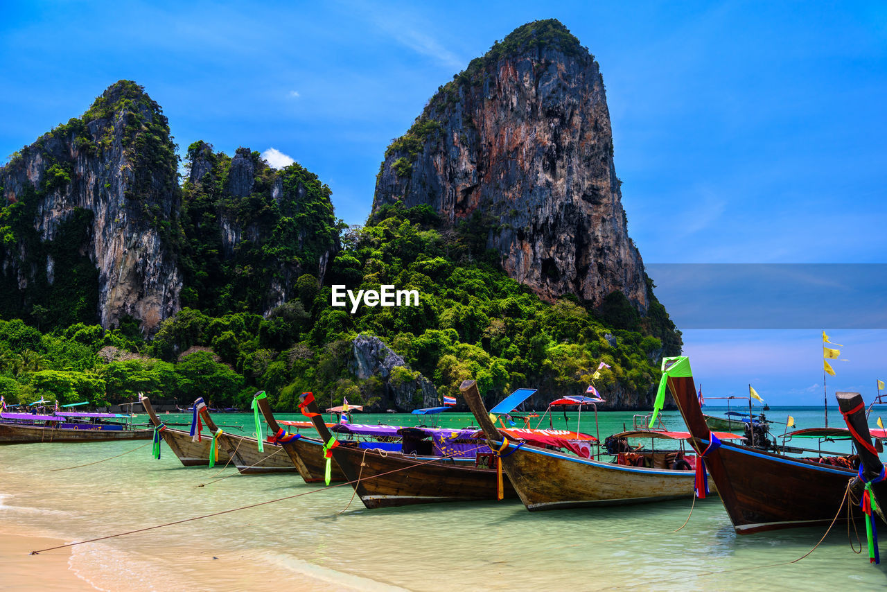 nautical vessel, water, transportation, mode of transportation, moored, sky, longtail boat, mountain, sea, nature, beauty in nature, day, rock formation, beach, land, rock, scenics - nature, mountain range, tranquility, no people, outdoors, formation, mountain peak, rowboat